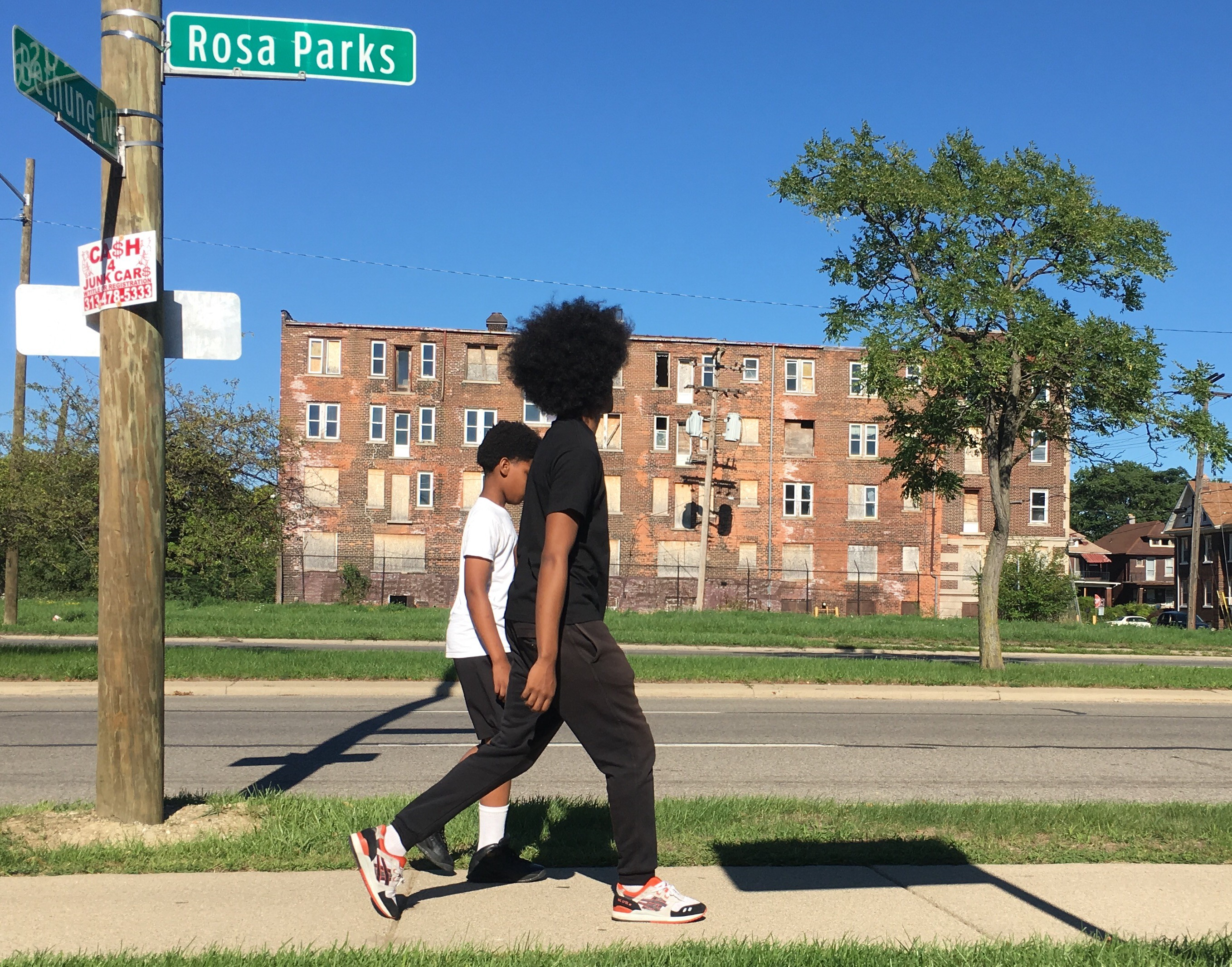 A photo of two Black youths walking down a street in Detroit.