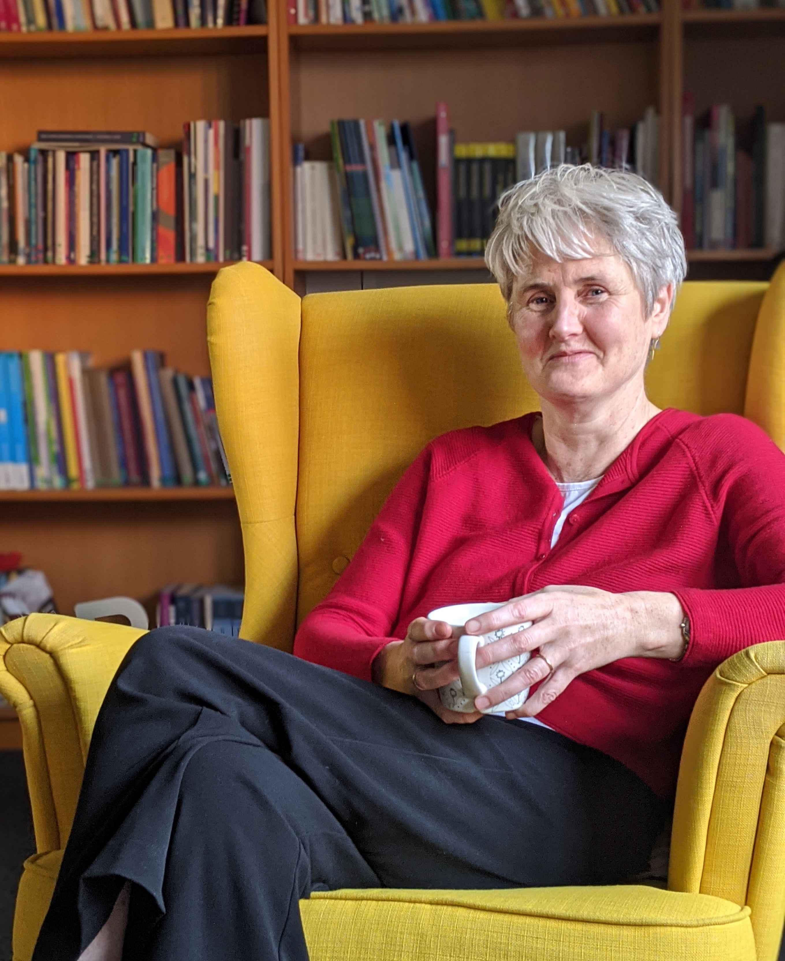 Patricia Penderville sitting on a yellow armchair.