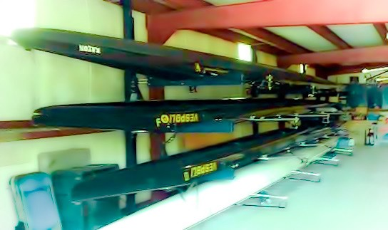 Several Vespoli eight-seater crew shells stored on racks in a boathouse.