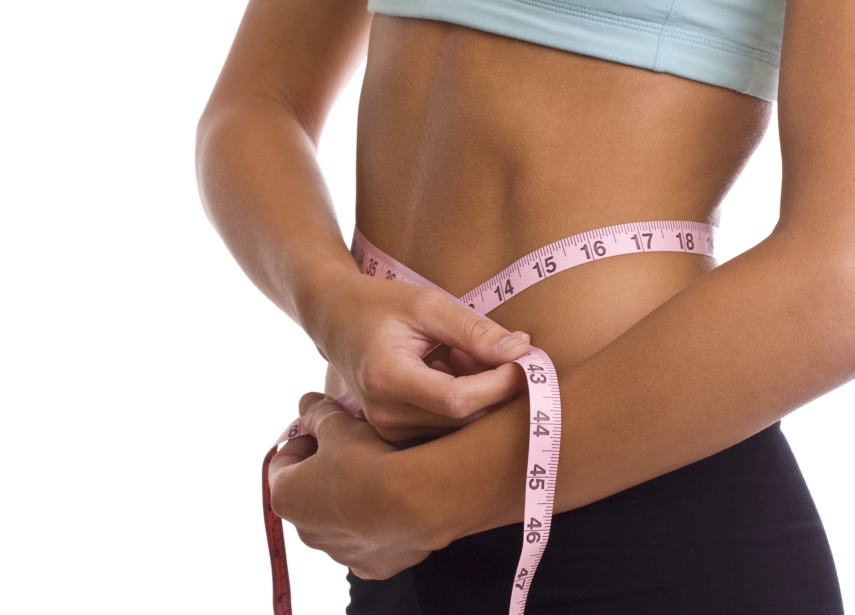 A thin woman measures her exposed waist with a flexible tape measure calibrated in inches.