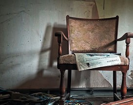 A newspaper left on an easy chair in a now-abandoned house.