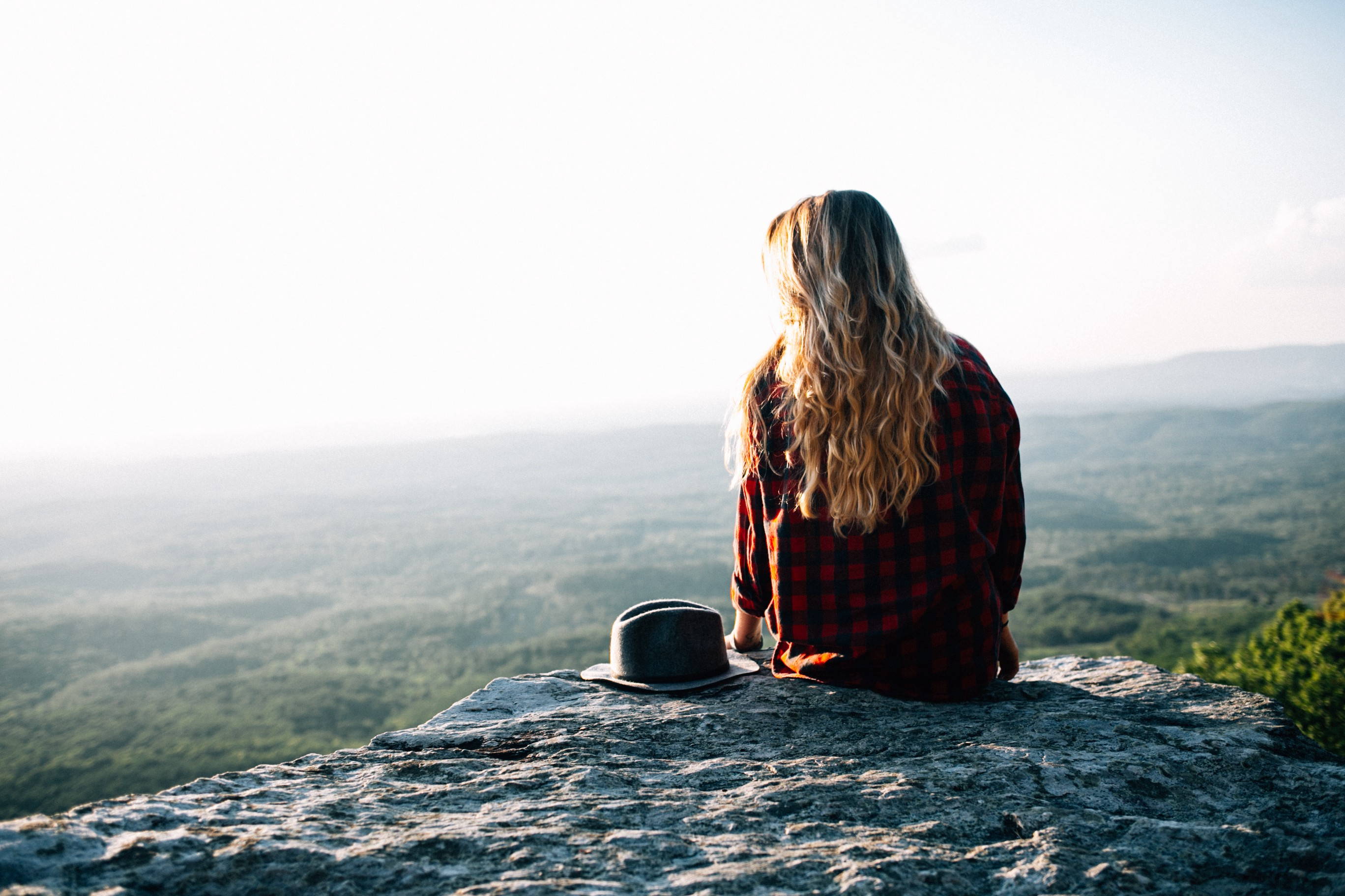 woman sitting on a rock overlooking a drop off, wondering