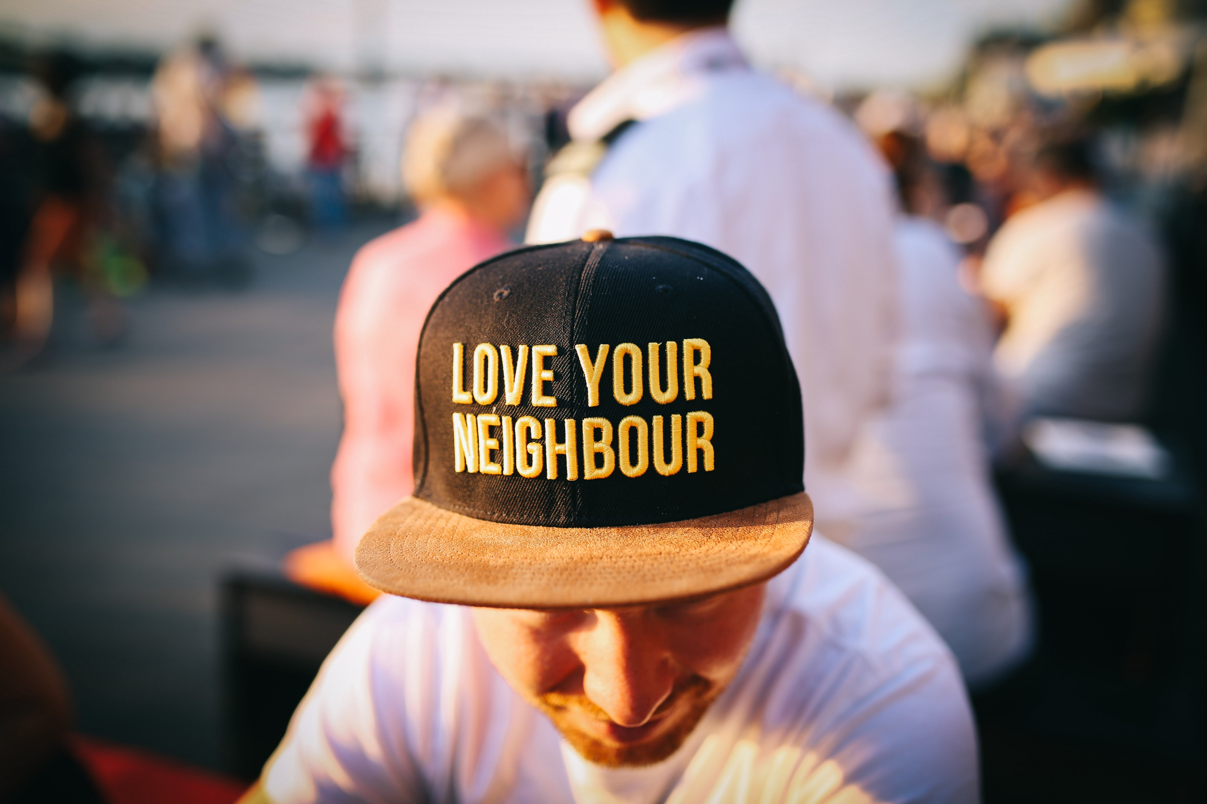 "Man with his back turned to people wearing hat that says, ""Love Your Neighbor."""