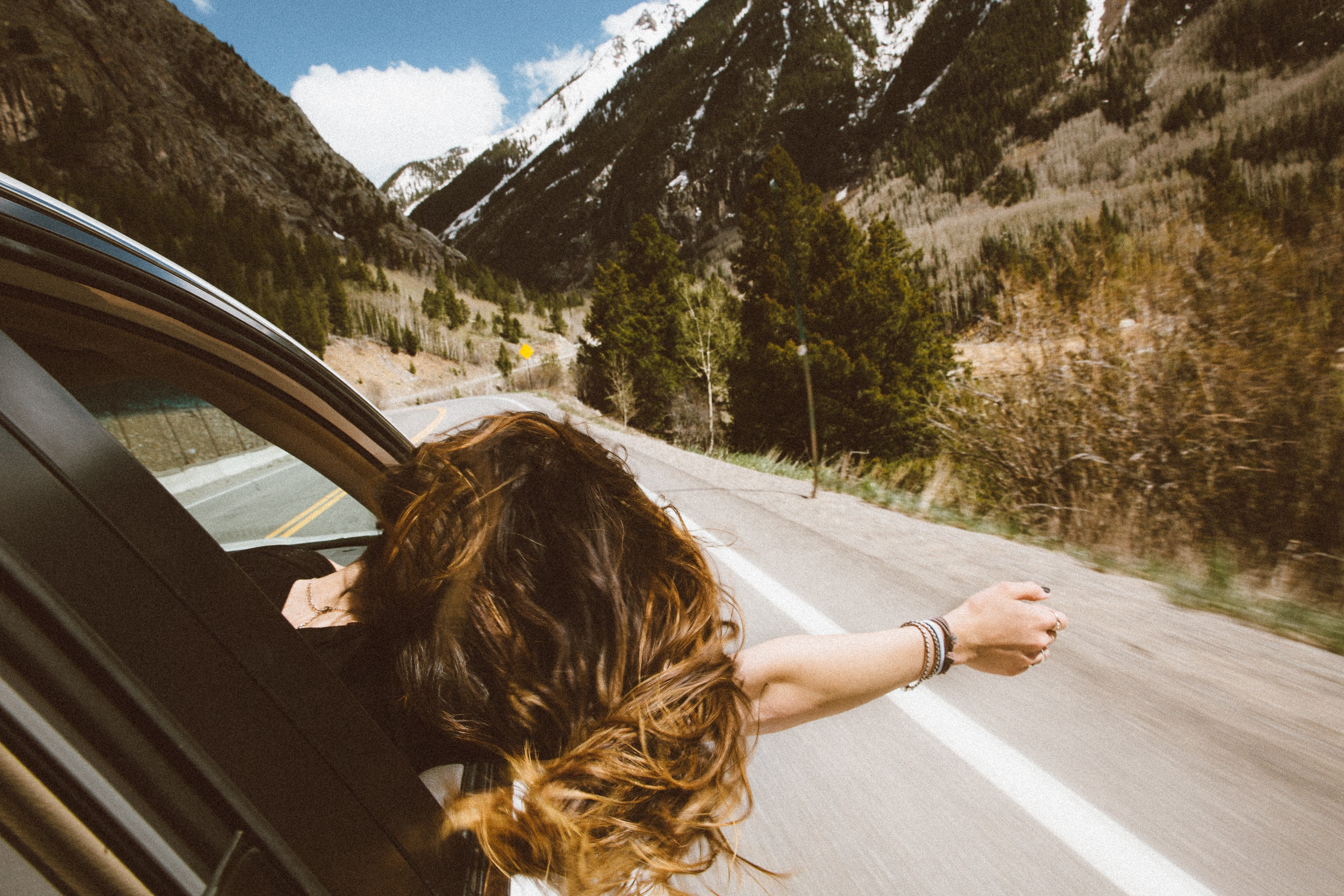 Riding in a car a girl sticks her head out the window savoring the wind through her hair and against the palm of her hand.