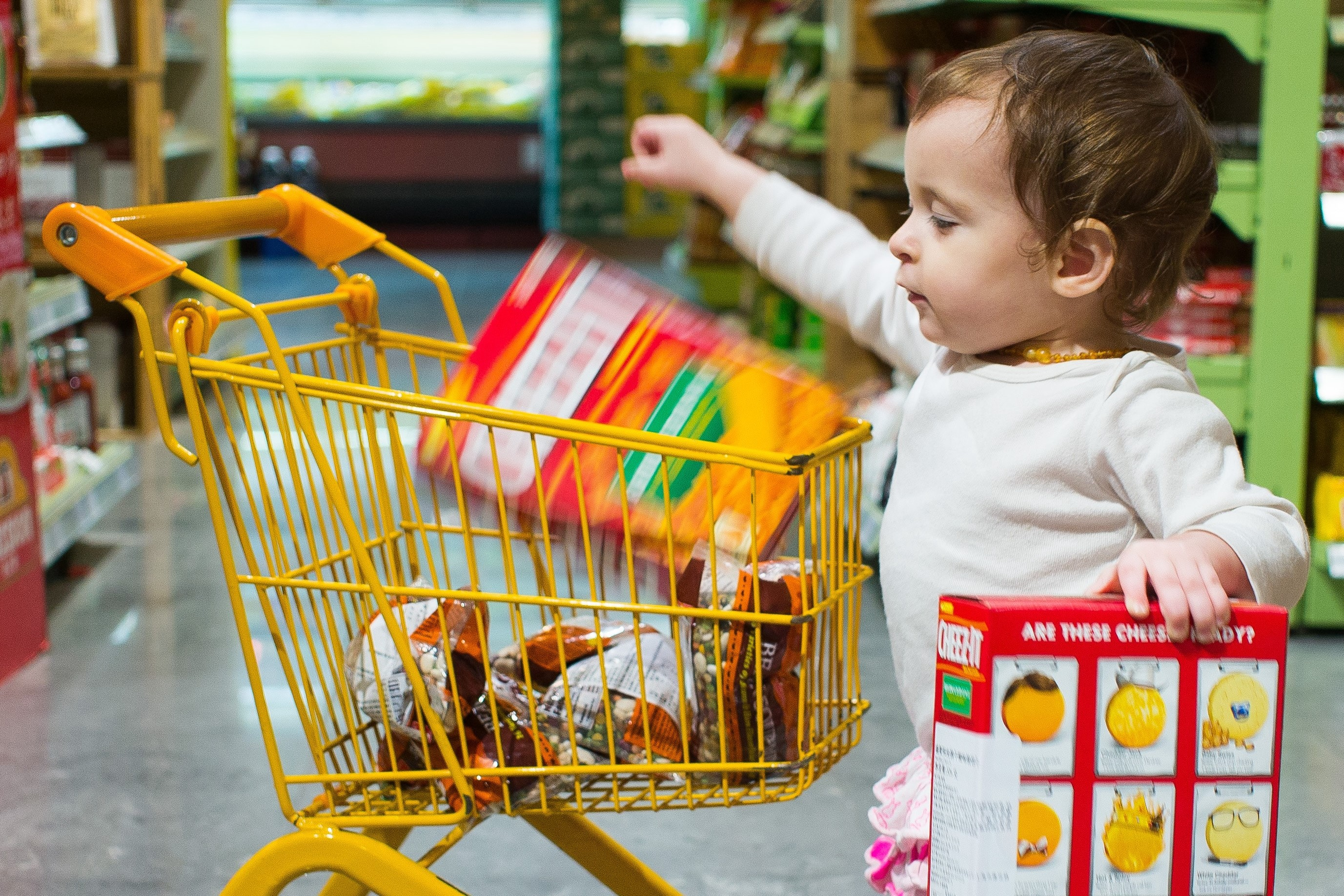 Toddler drops box of crackers into a small yellow shopping cart in a grocery store