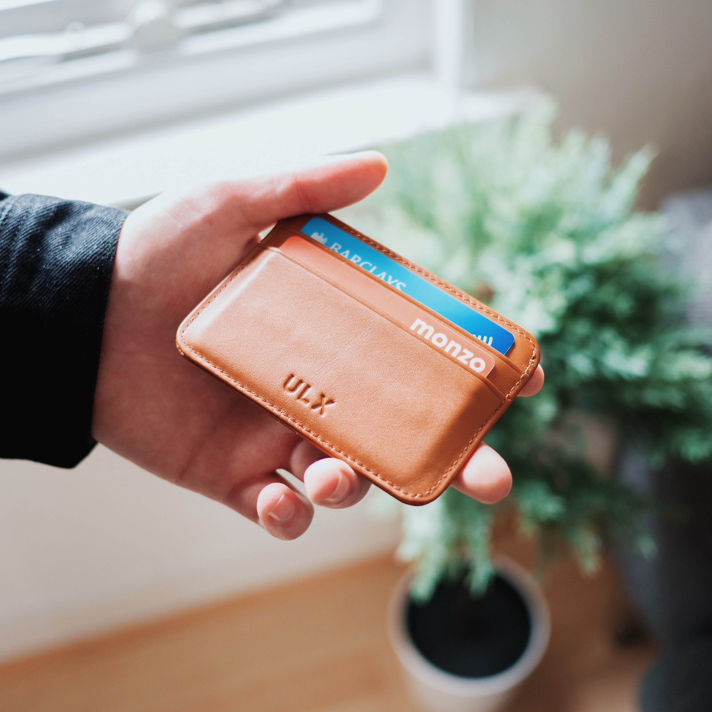 Man holding a leather wallet containing a monzo and barclays card