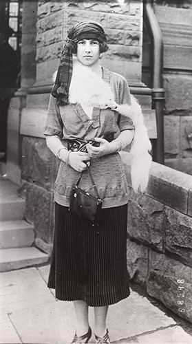 Xenia wearing a short-sleeved cardigan, mid-calf skirt, turban, and fox stole.