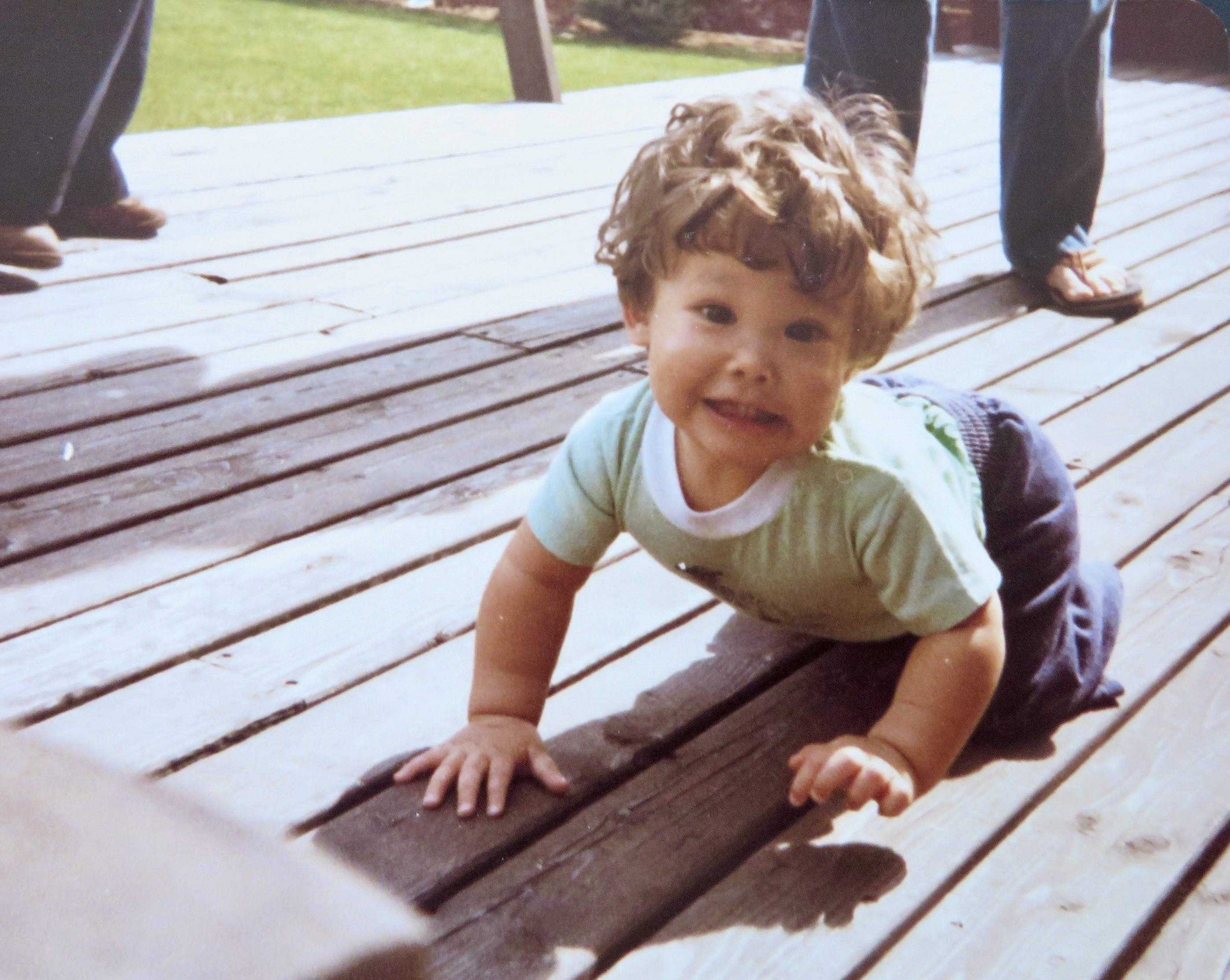 9 month old Amy smiling and crawling on a wooden deck.