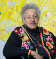 A portrait of Howardena Pindell in front of a colorful art piece.
