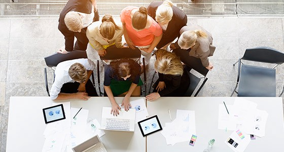 A team of coworkers looking at a computer