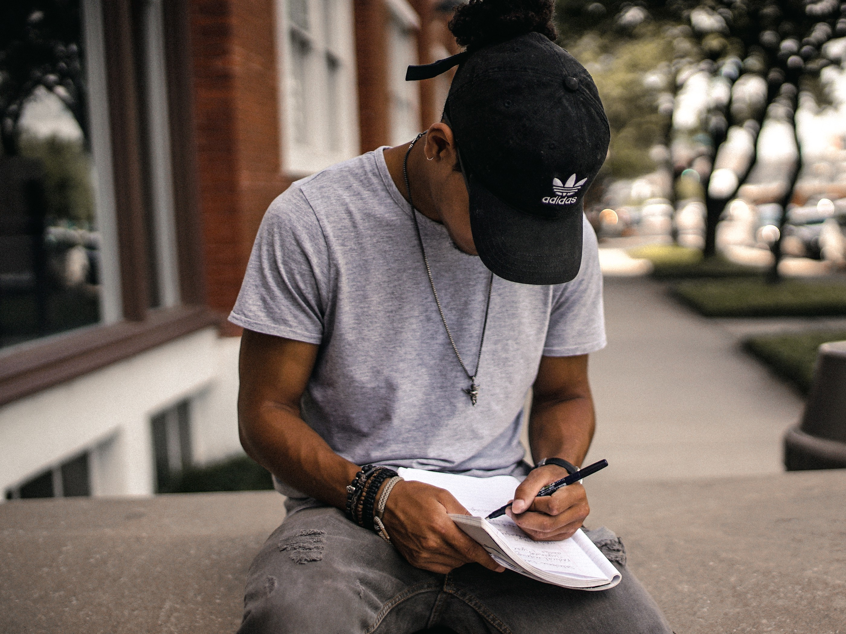 A young man writing in a notebook on a bench.