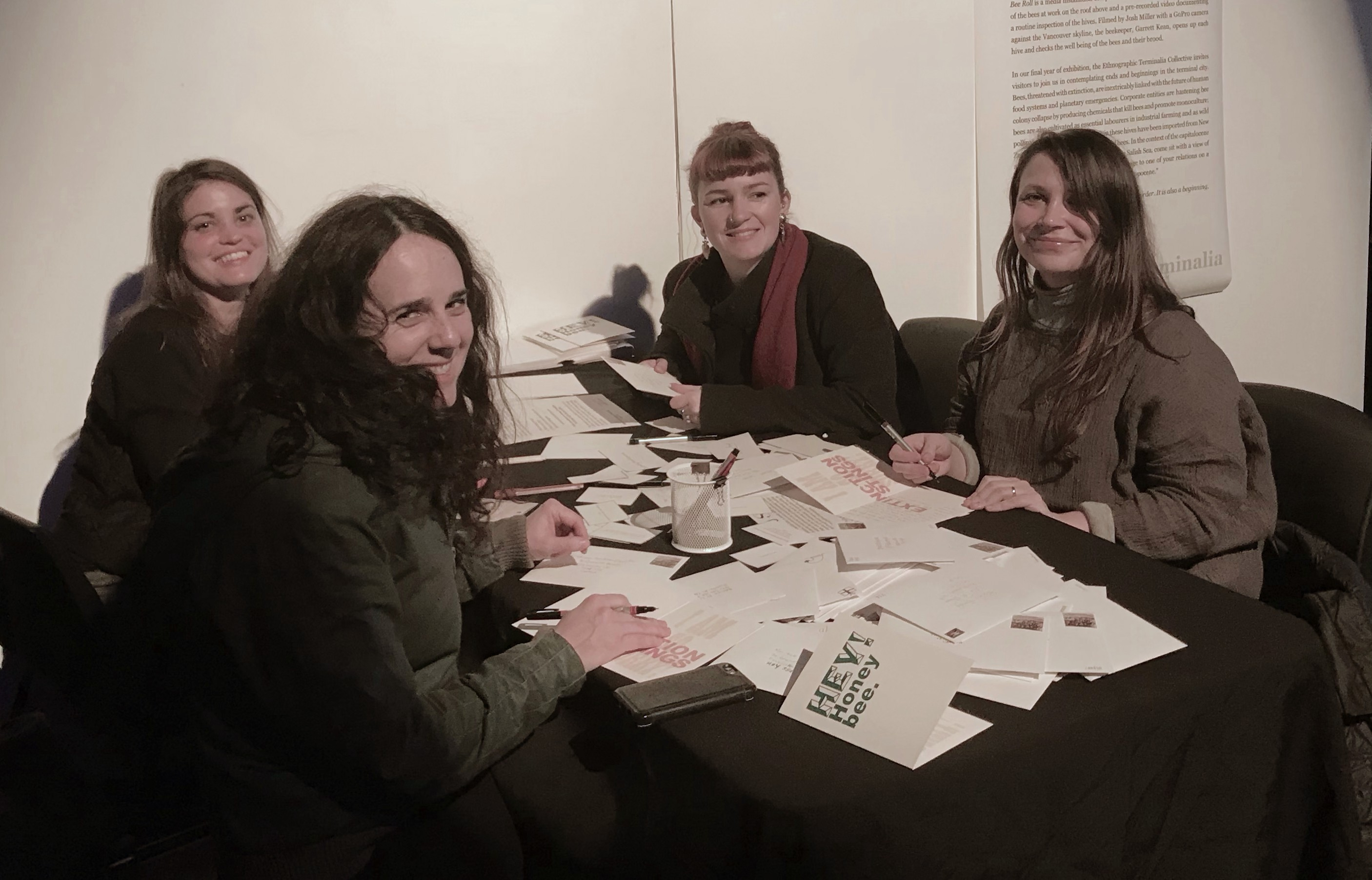 """A group of gallery visitors pull writing prompts and compose messages on """"Hey, Honey Bee!"""" greeting cards in Vancouver, BC."""