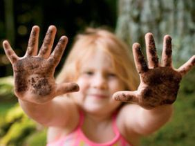 Young girl showing dirty hands.