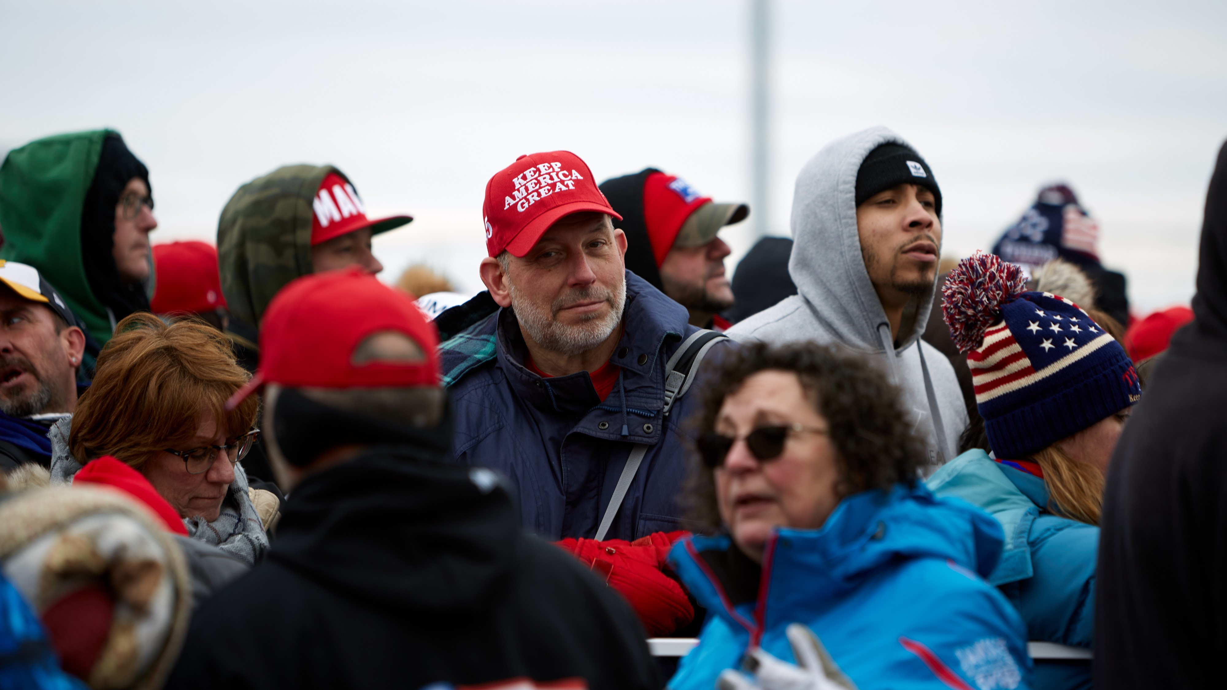 Trump supporters, one man wearing a MAGA hat.
