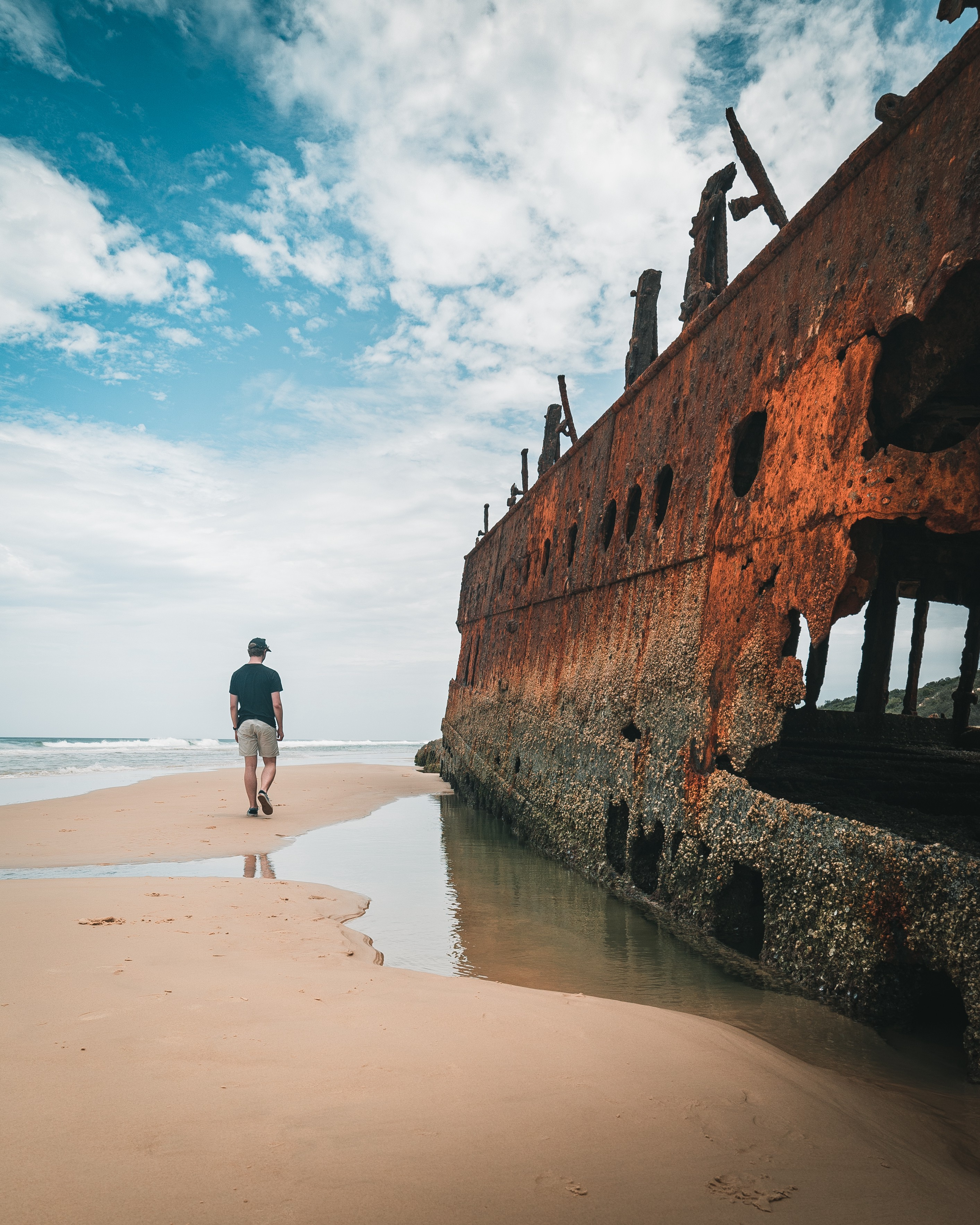 A person walking on a beach next to a rusted ship. The rust is so severe that it seems to have rusted a large hole in the ship.