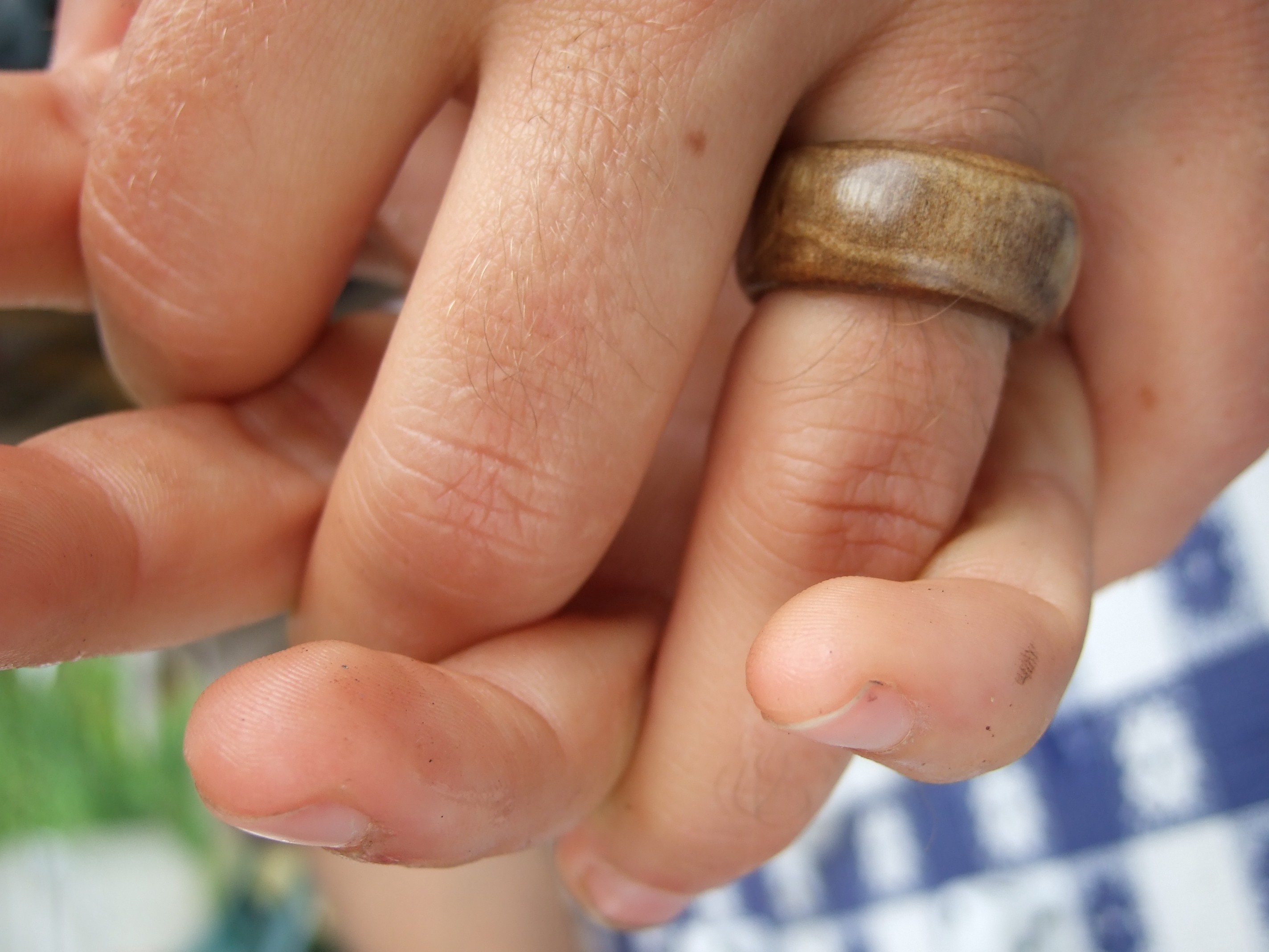 Two hands intertwined, one wearing a wooden ring