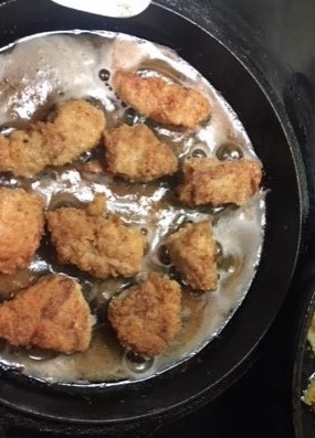 Pheasant nuggets cook in a cast iron skillet