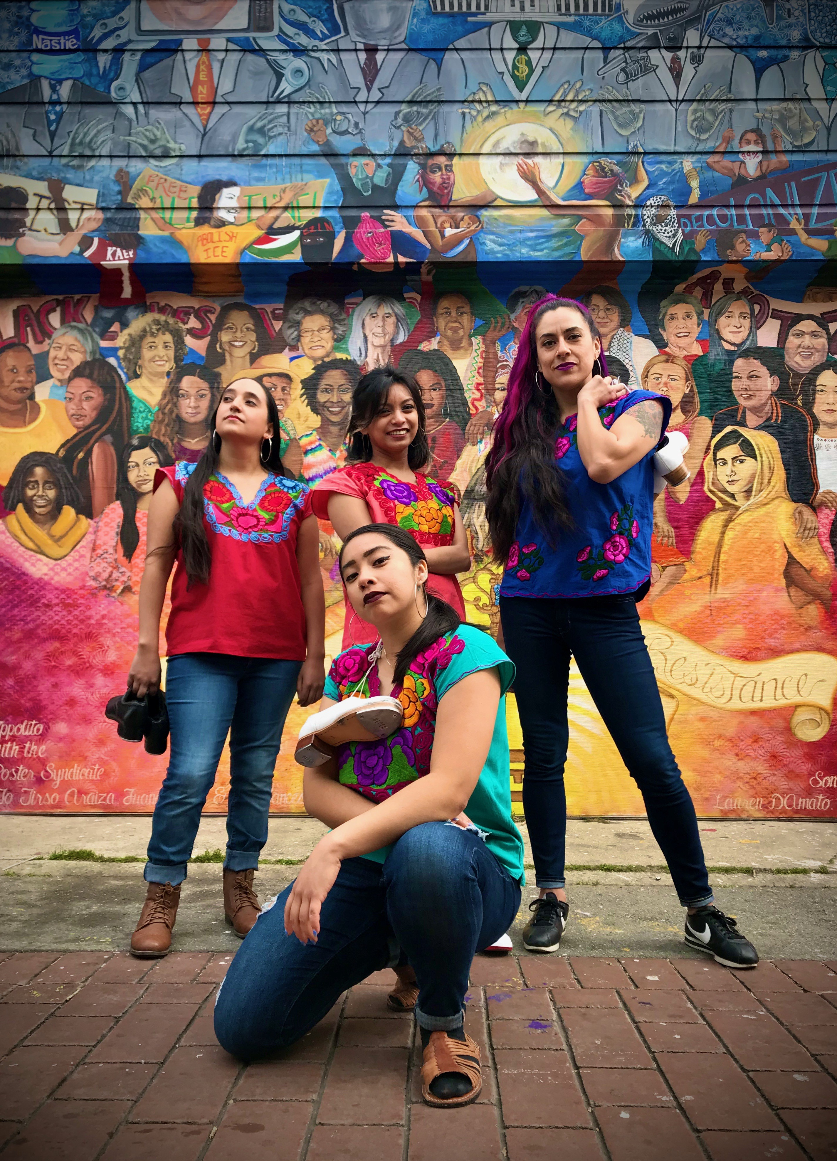 Four women pose in front of street mural