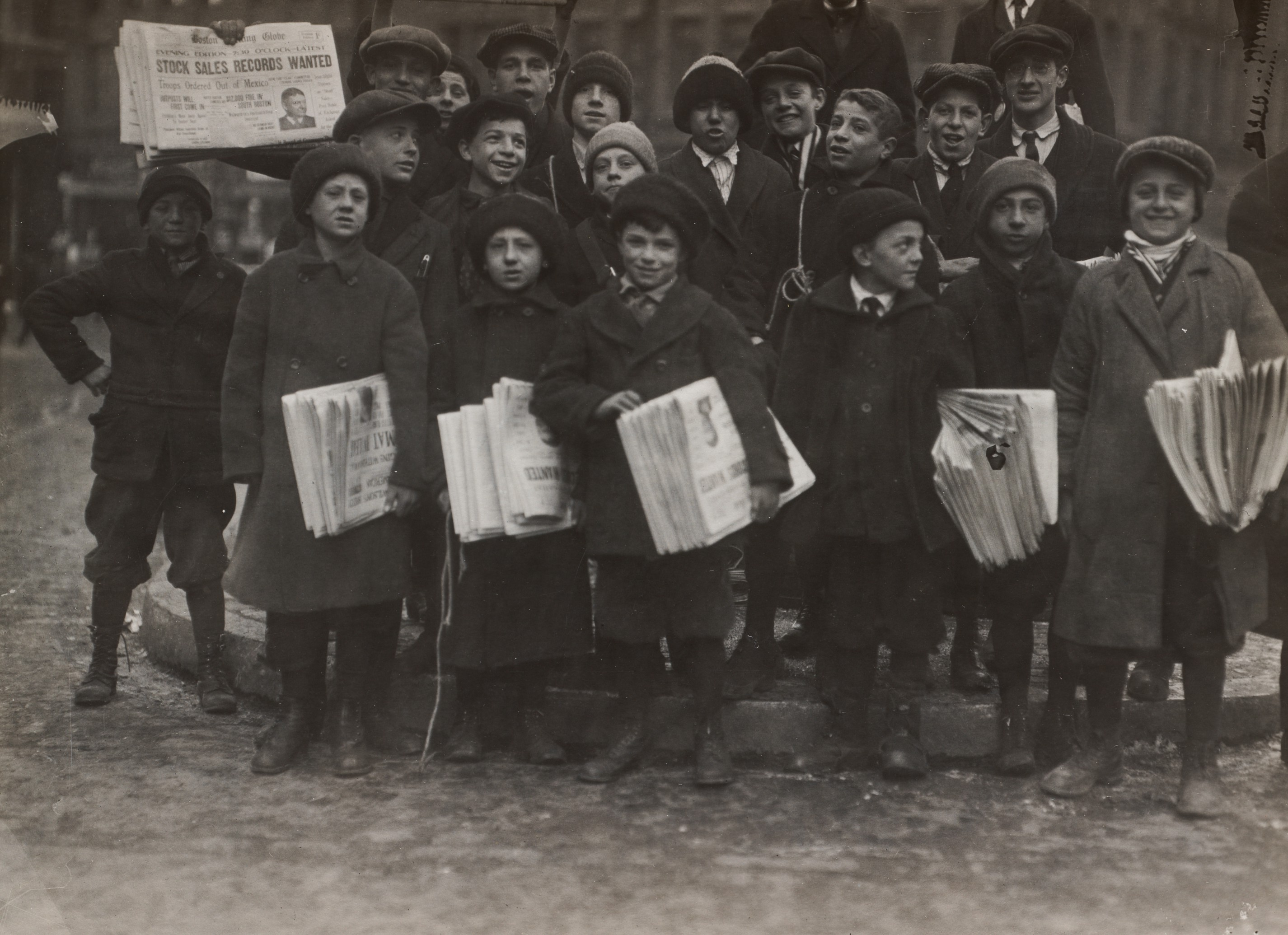 A group stands on a street, with some holding stacks of newspapers.