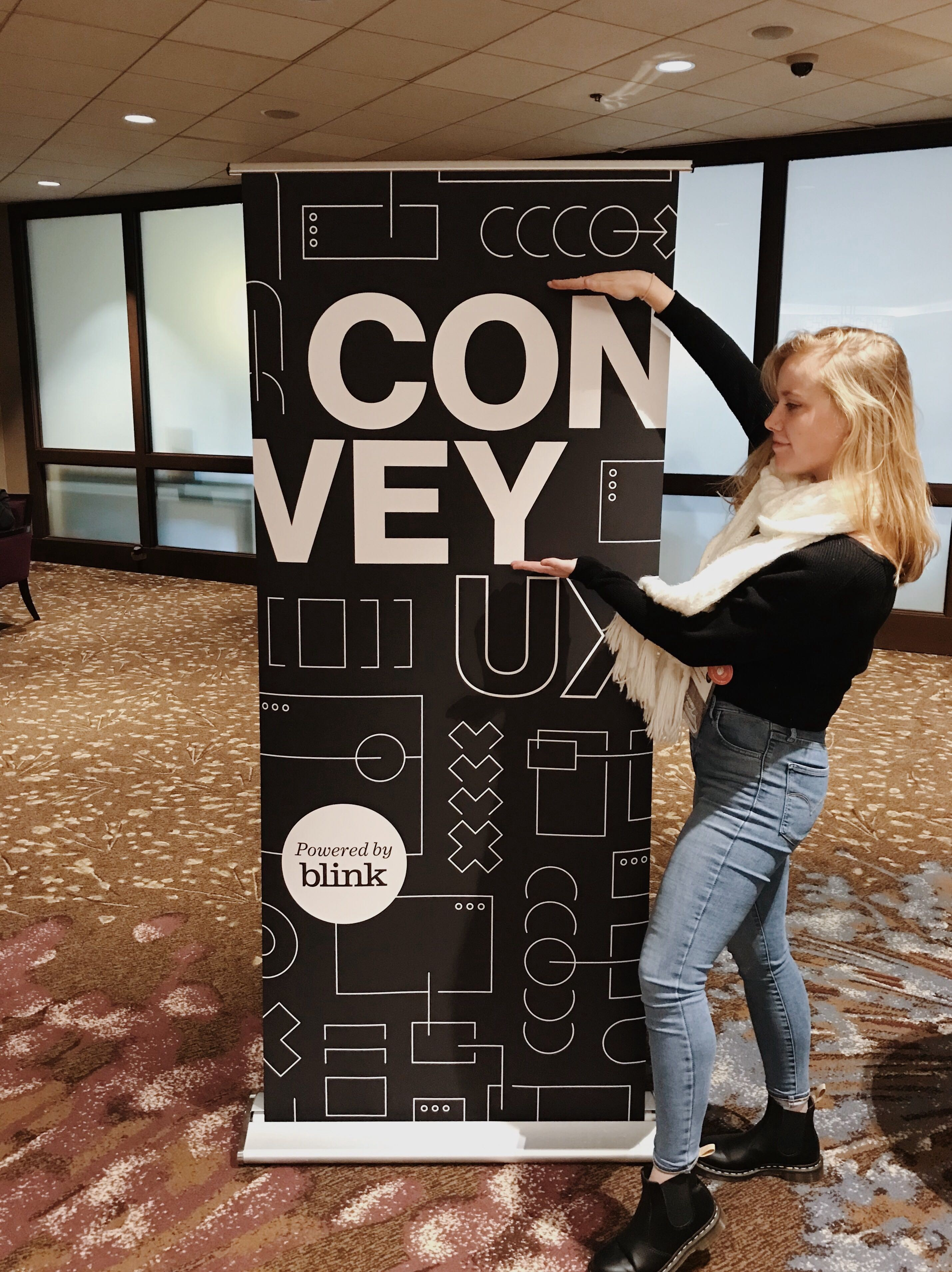 "Julianne poses next to a tall poster that says ""Convey UX, powered by Blink"""