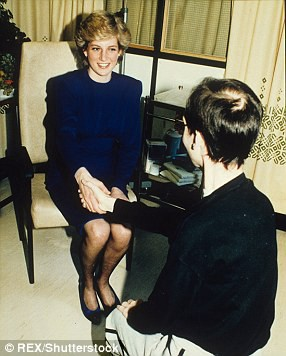 Princess Diana of Wales, smiles, wearing a blue dress, shakes hands with an AIDS patient whose back is to the camera.