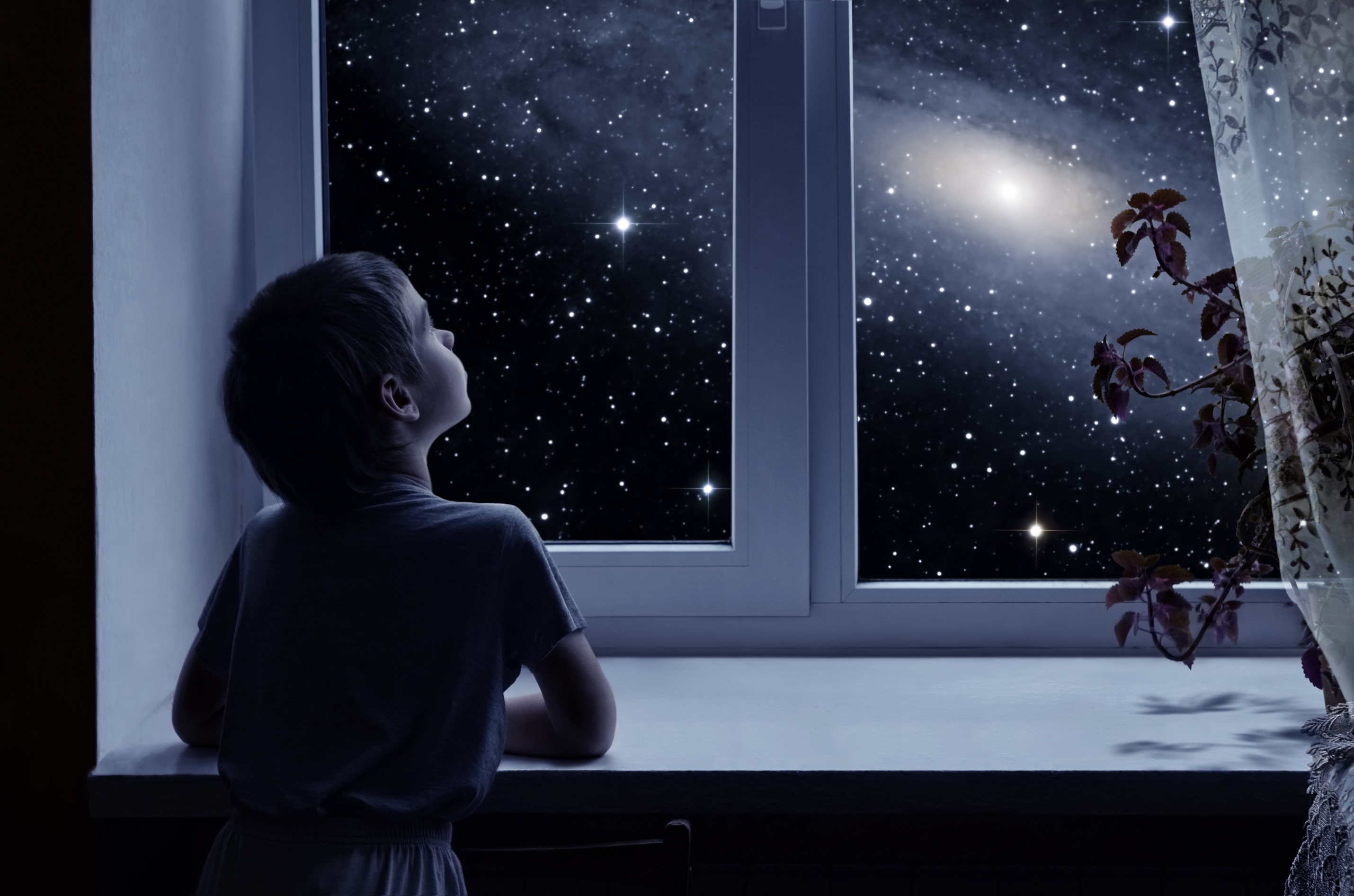 Child looking out window at starry sky.