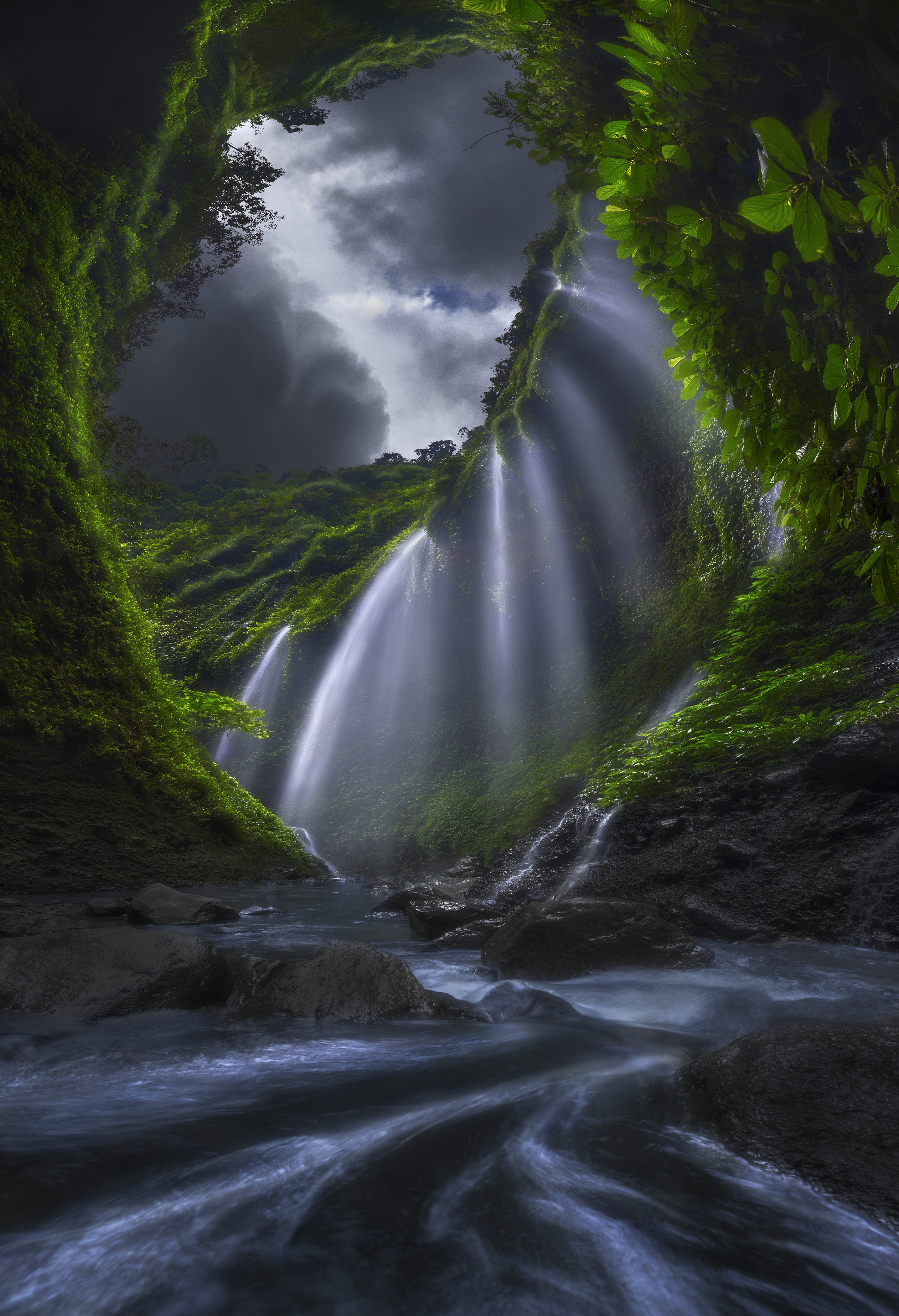 A fine art photo from the perspective inside a cave or hiding place, showing green hills and white light streaming in
