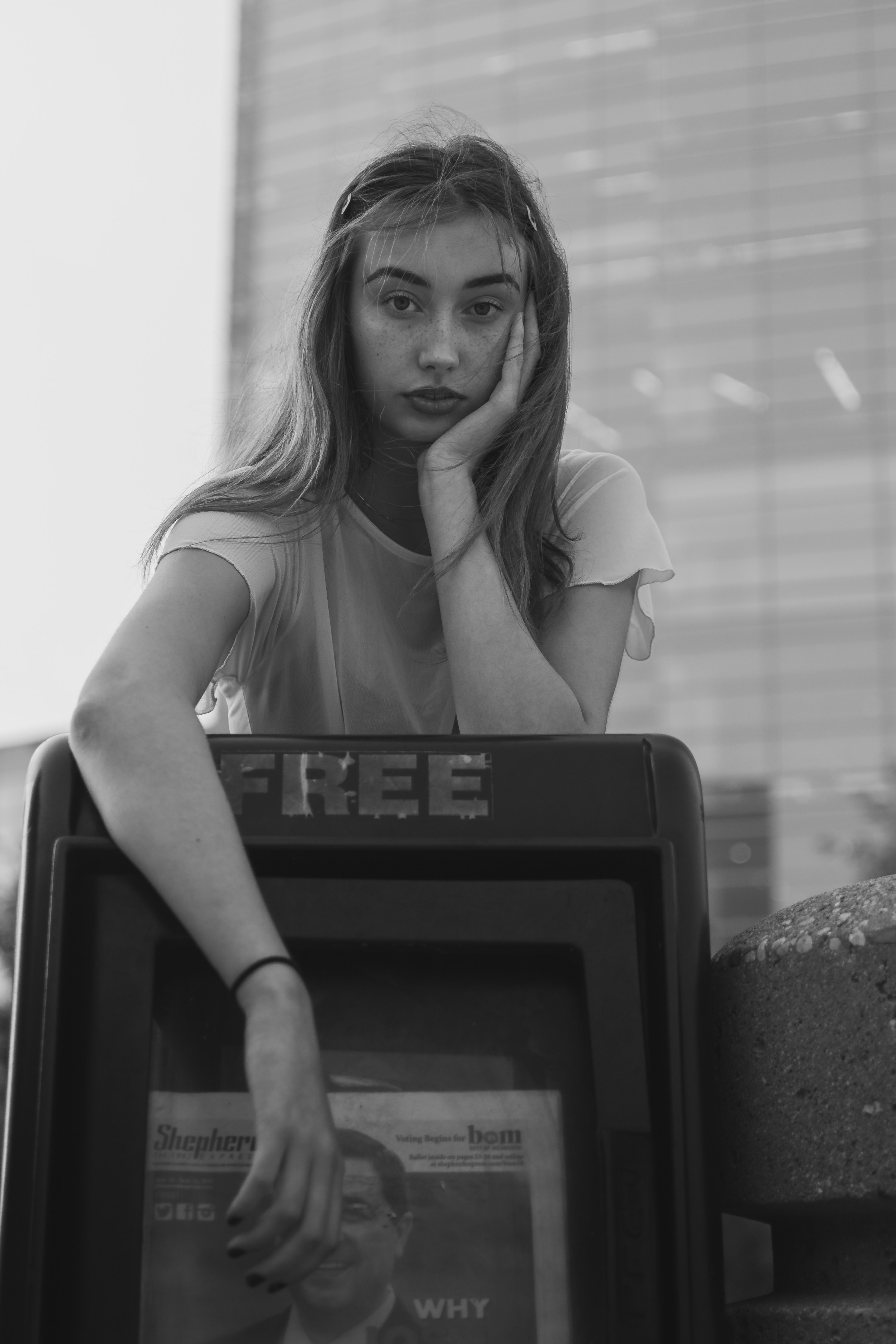 Black and white of young woman leaning over a free newspaper stand with one hand on her cheek.