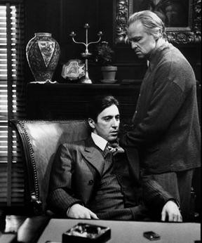 """Photo from the movie """"The Godfather"""" depicting Michael (seated) and Vito (standing behind him)"""