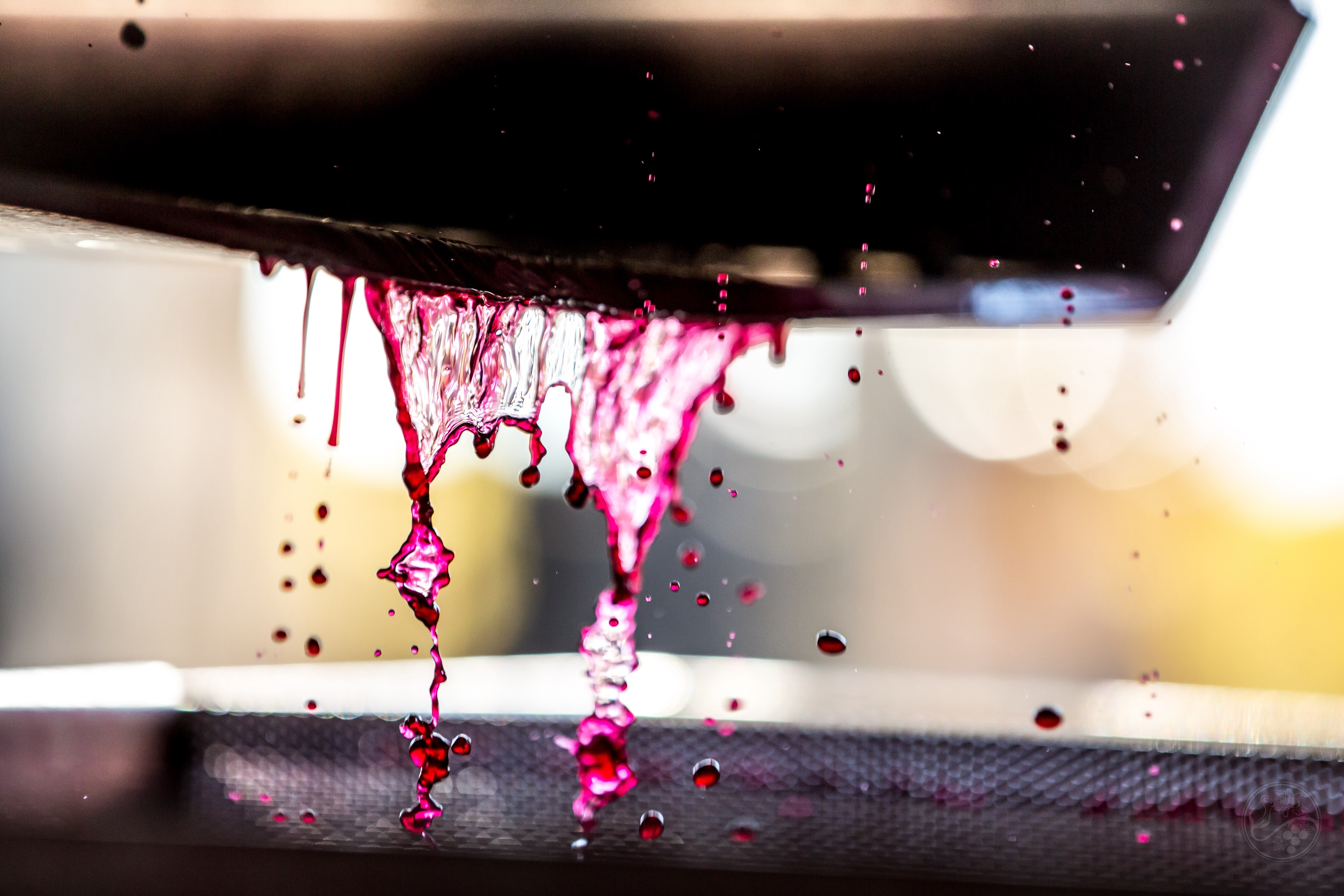 Deep purple juice falls from a container.