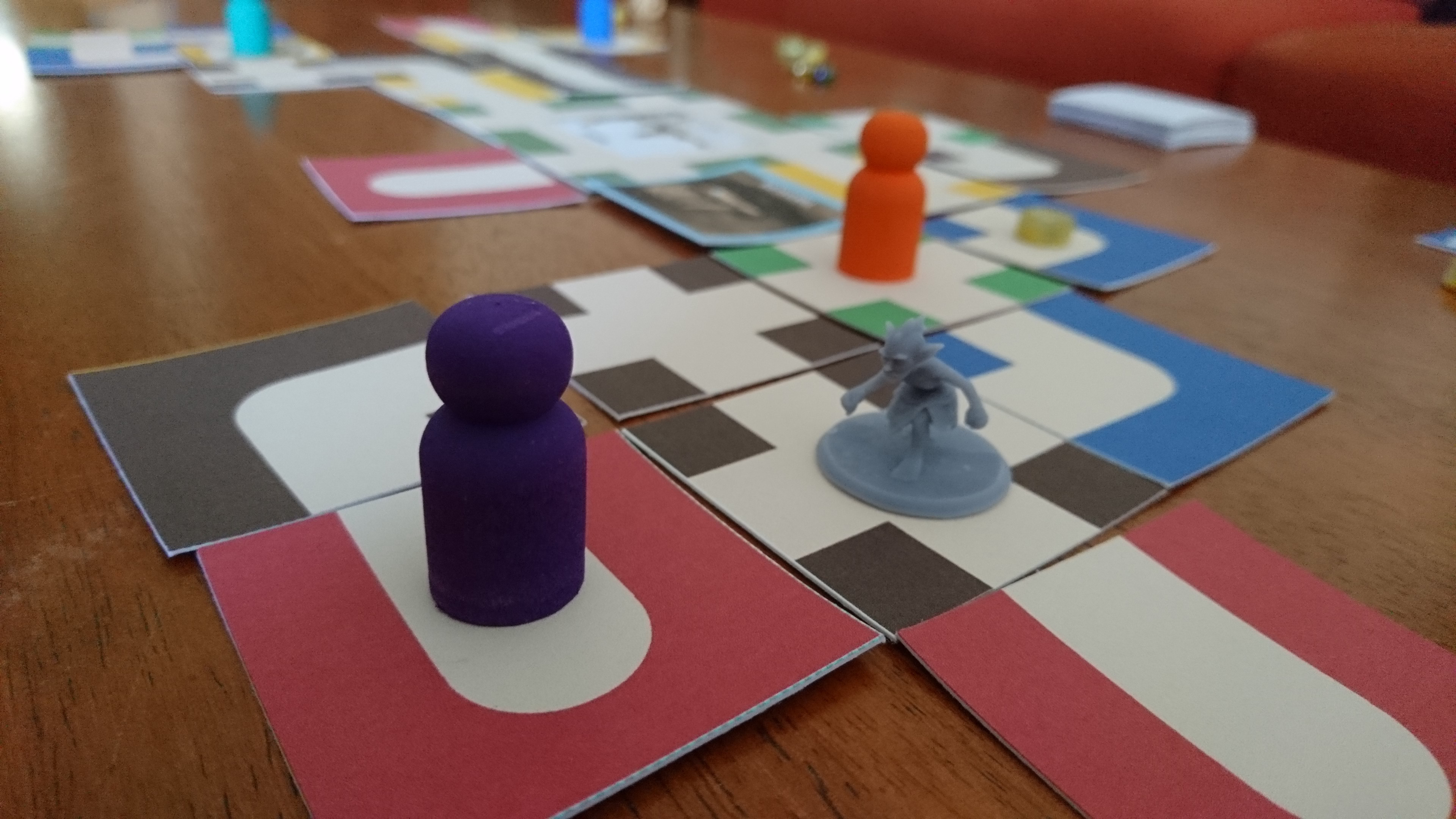 The feelings game: A purple pawn and a grey gremlin on brightly coloured maze tiles.
