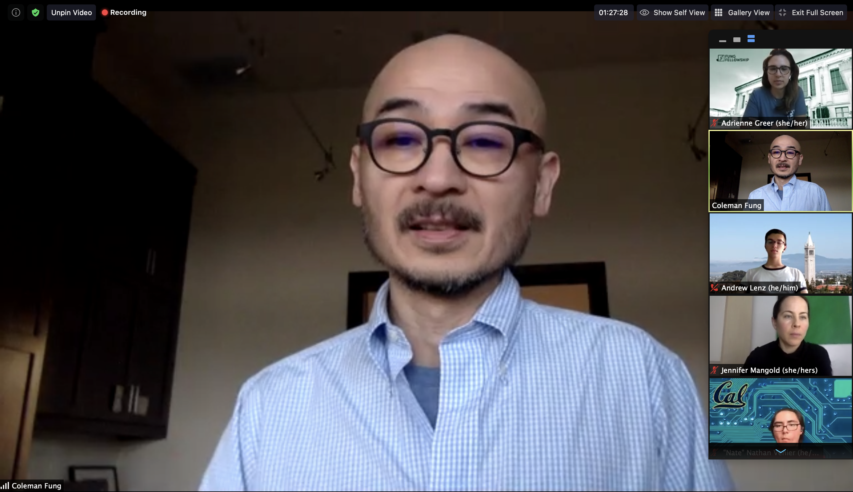 Screenshot of a Zoom call with a bald man in glasses and a light blue button down speaking.