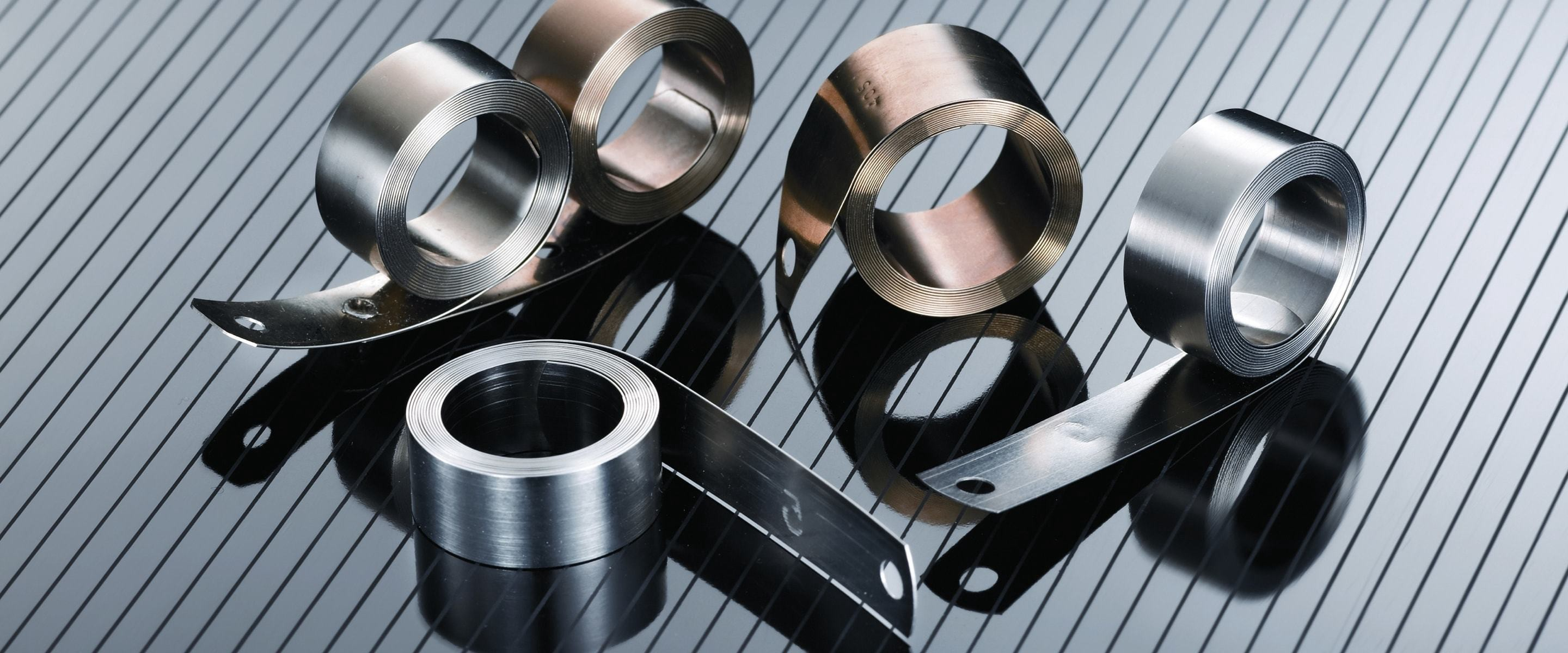 Five sheet rolls of Ulbrich Stainless Steels & Special Metals, Inc metal. Three of the five rolls are silver and two of the five rolls are bronze.