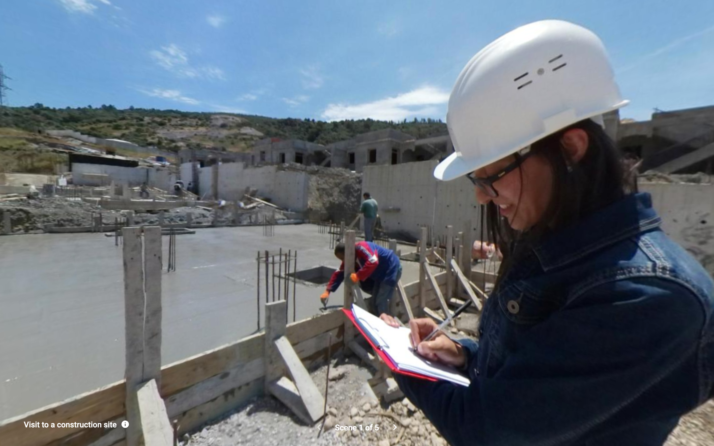 A woman in a white helmet writes on a clipboard while a construction worker smooths cement in the background.