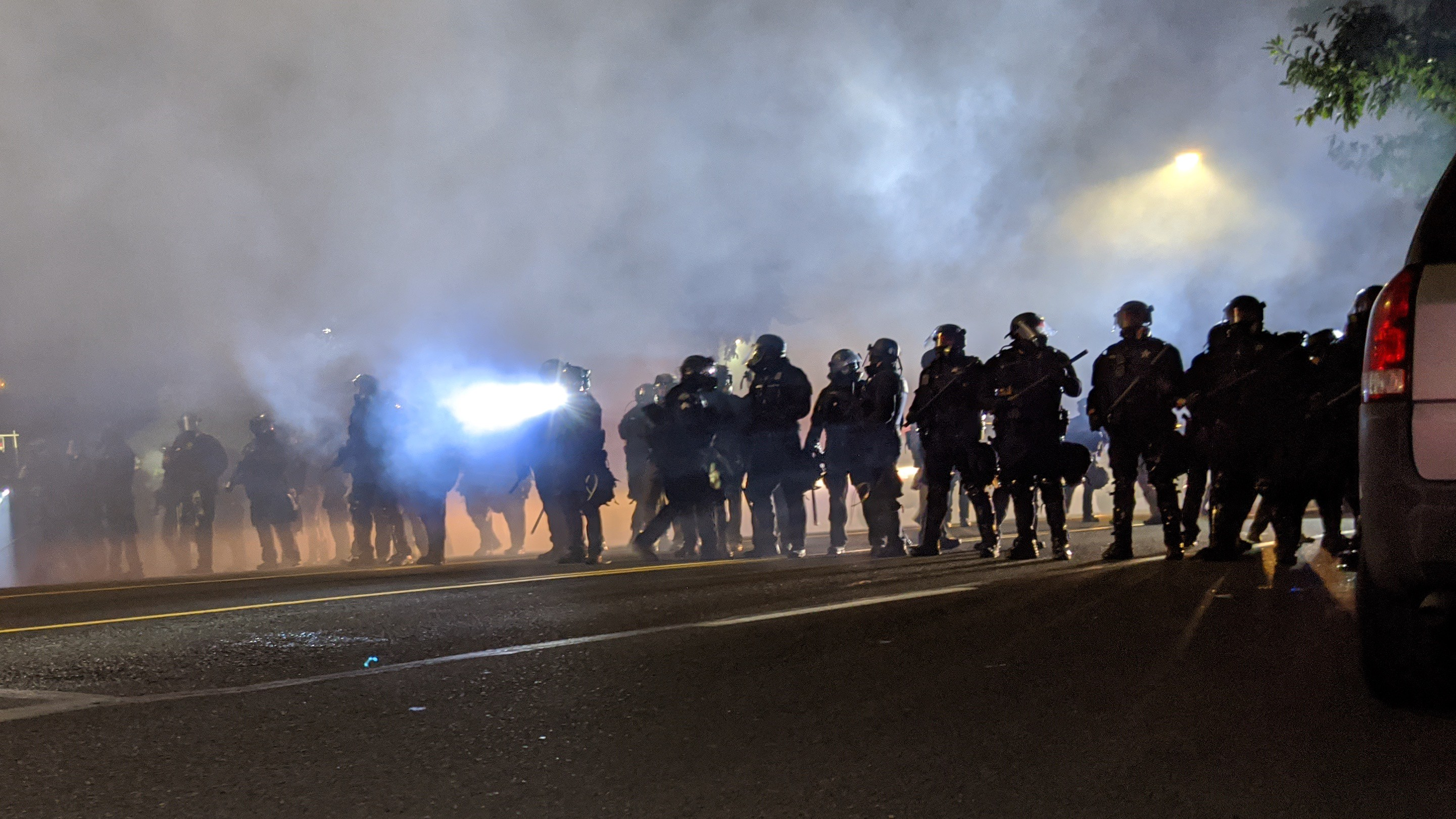 A line of police officers in riot gear standing in clouds of tear gas. They wear gas masks and carry batons and weapons