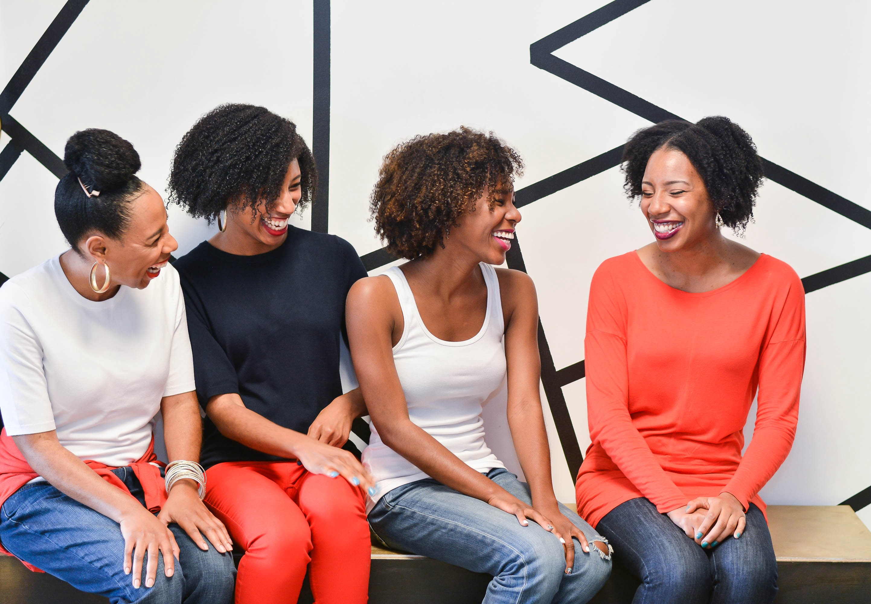 Group of natural hair black women laughing and talking