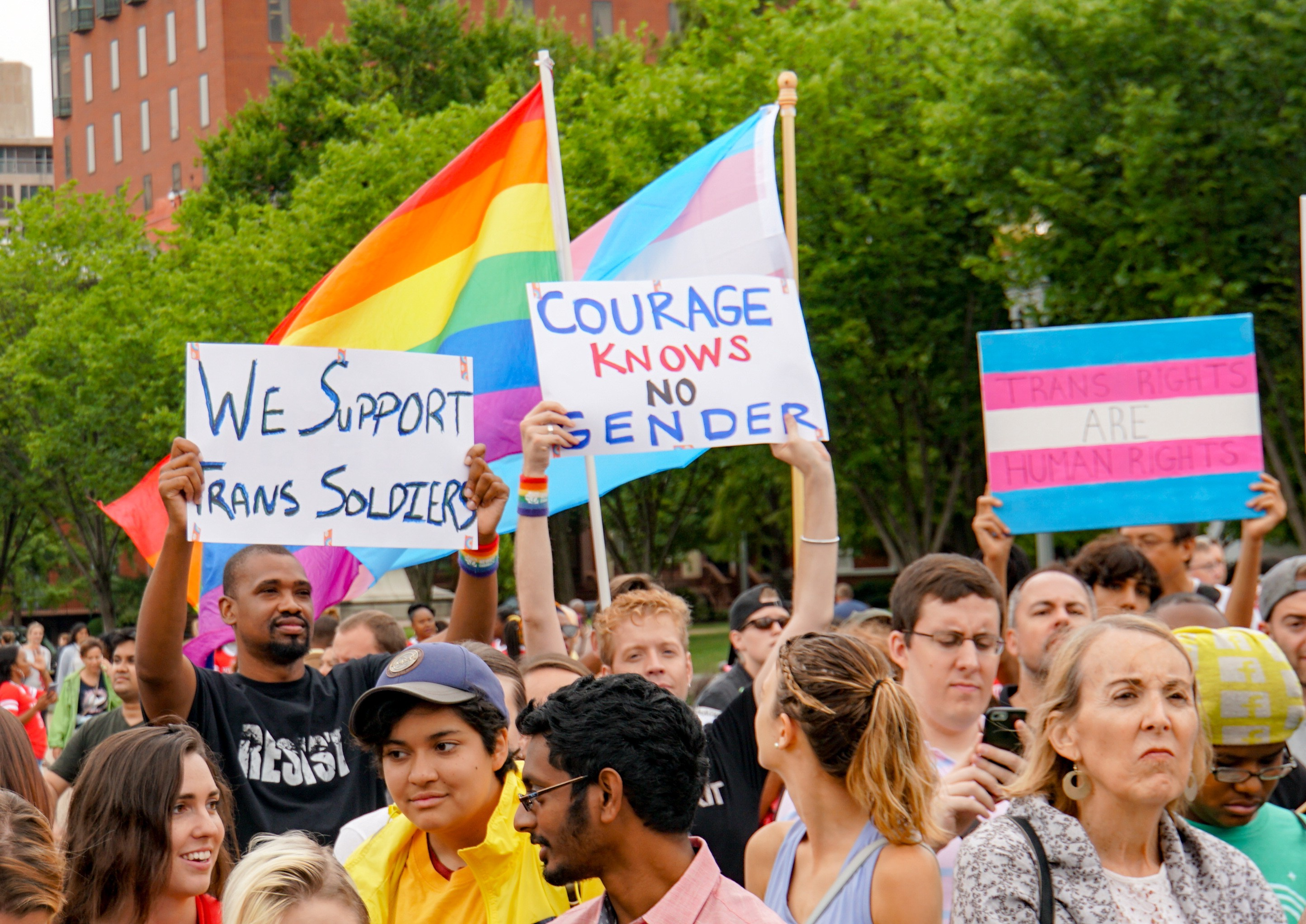 3 protest signs read: We support trans soldiers. Courage knows no gender. Trans rights are human rights.