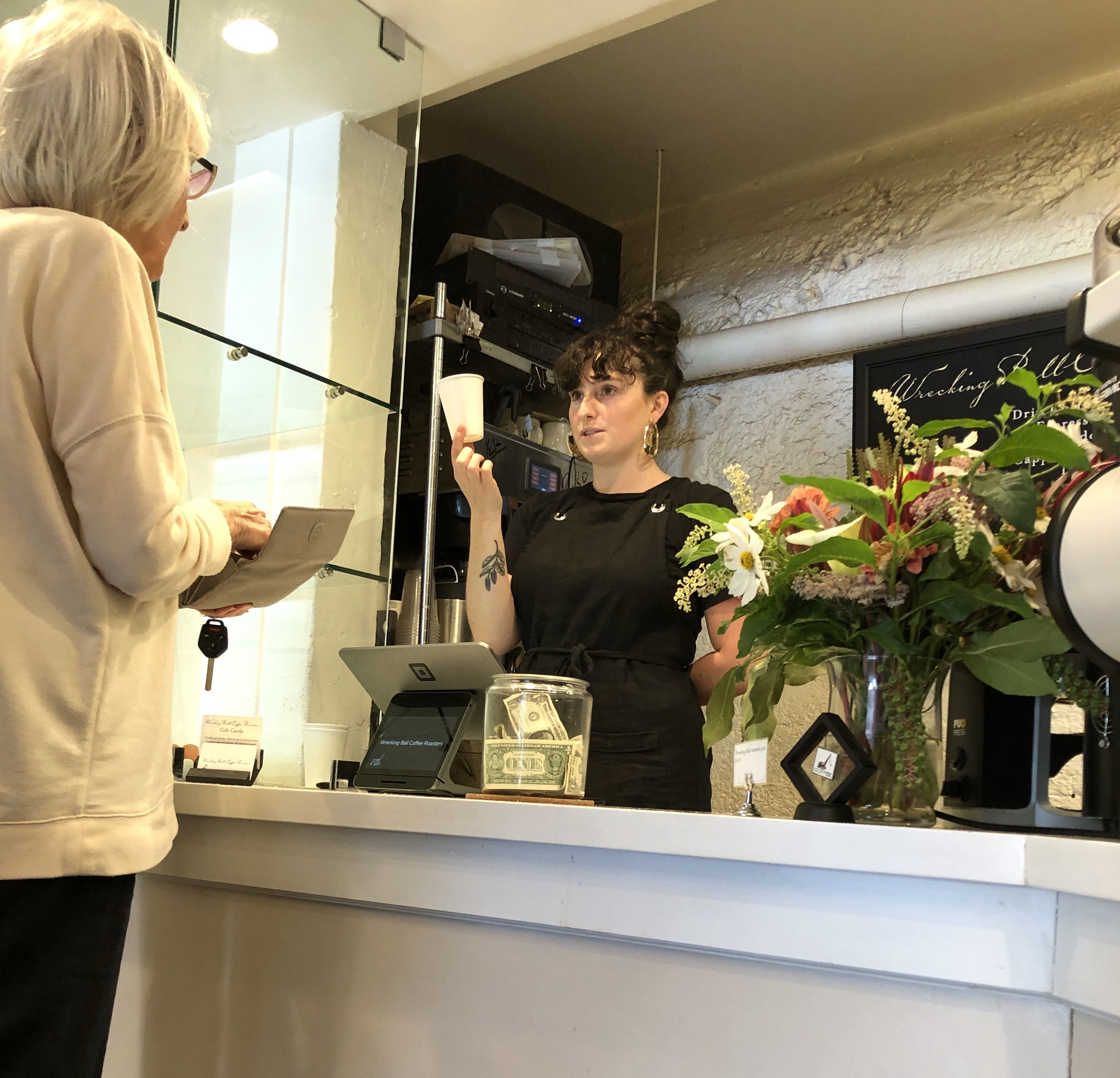 A young woman behind a cash register is holding up a cup for a woman to see.