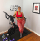 """A photo of Teresia Greer and her Peloton bike in her living room. """"Life is short, do stuff that matters"""" is on her wall."""