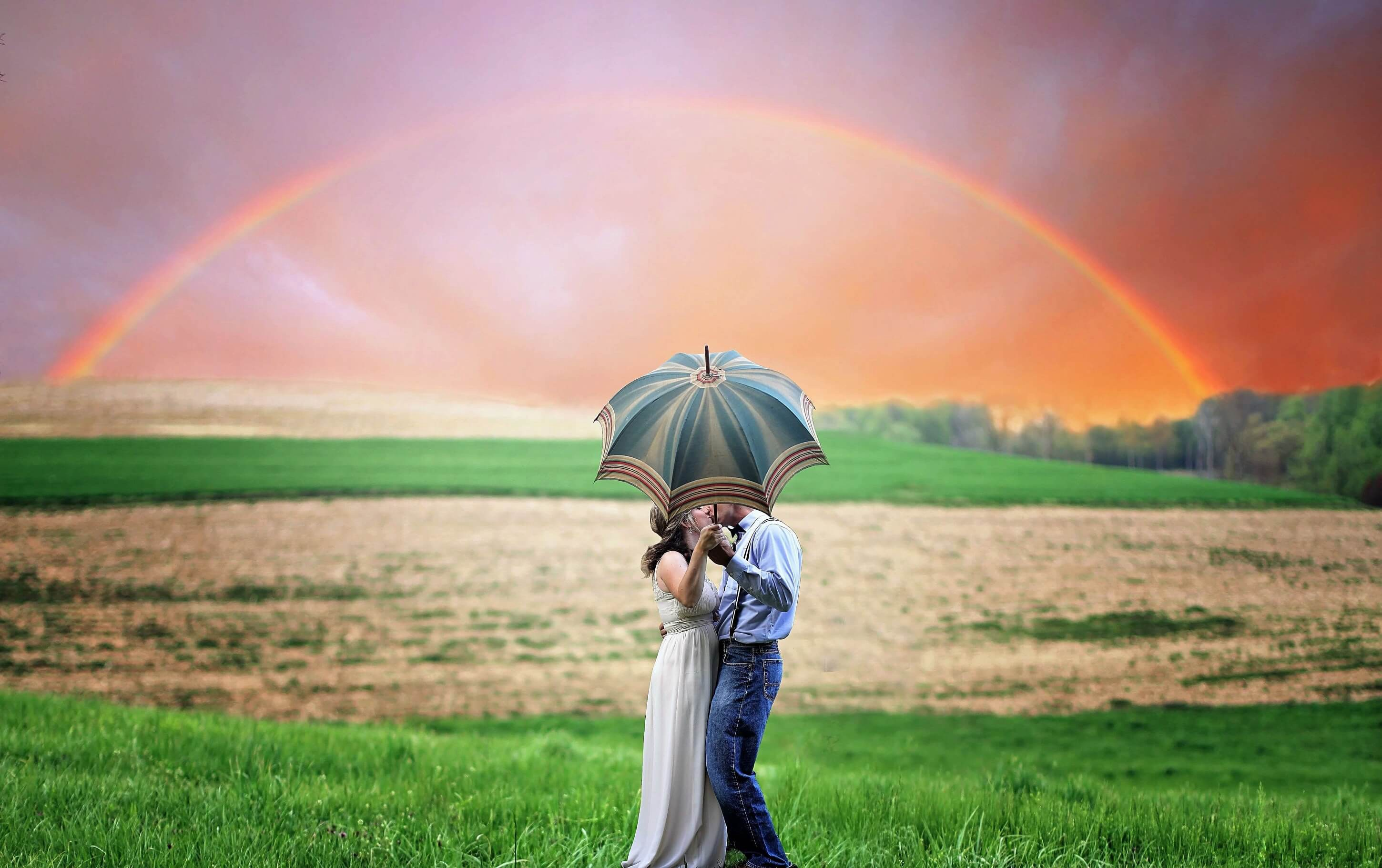 Evoking the concept behind Finneas debut album 'Optimist', the image shows a couple kissing on a field under an umbrella with a rainbow in the background