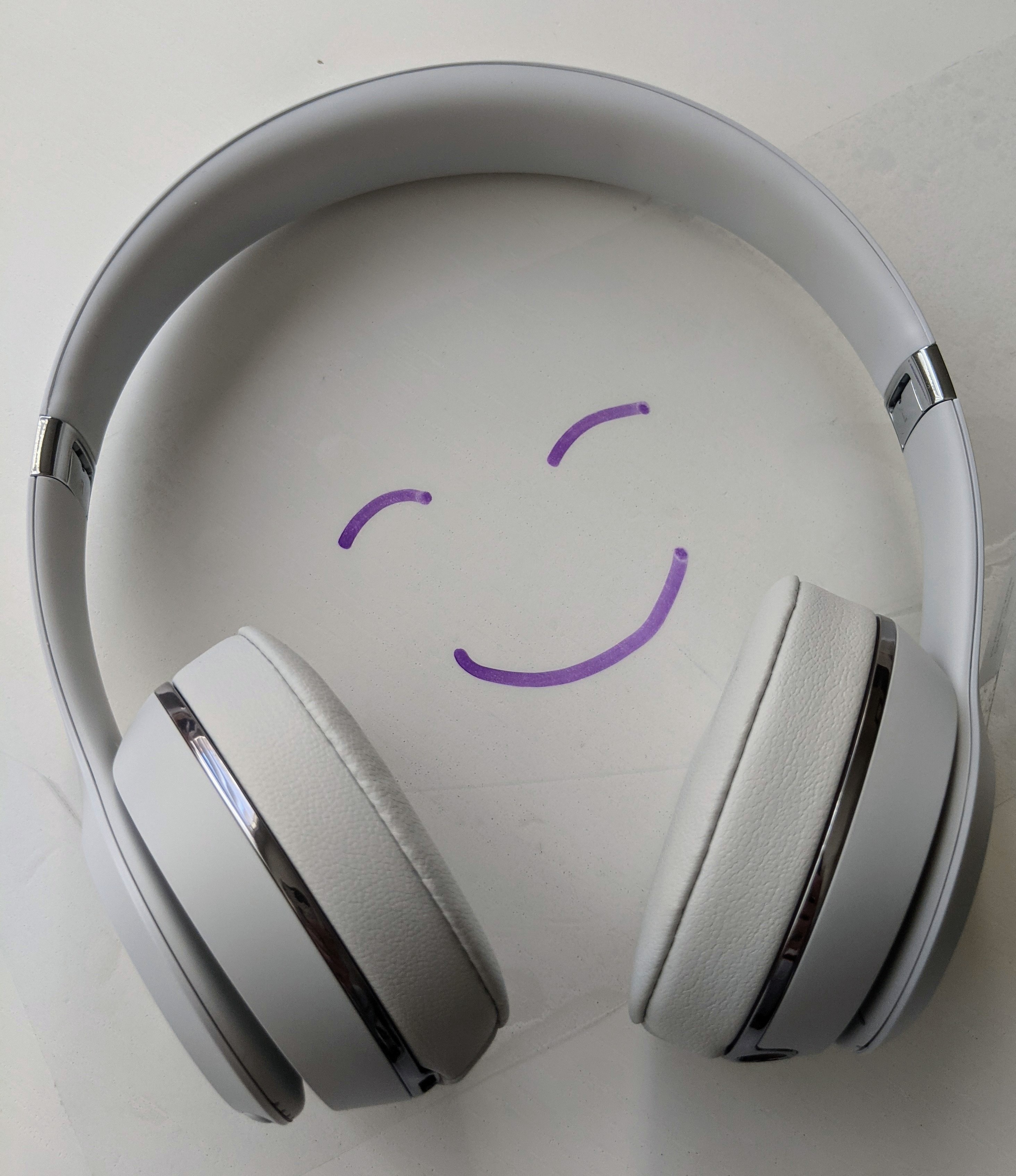 White pair of headphones with purple smiley face