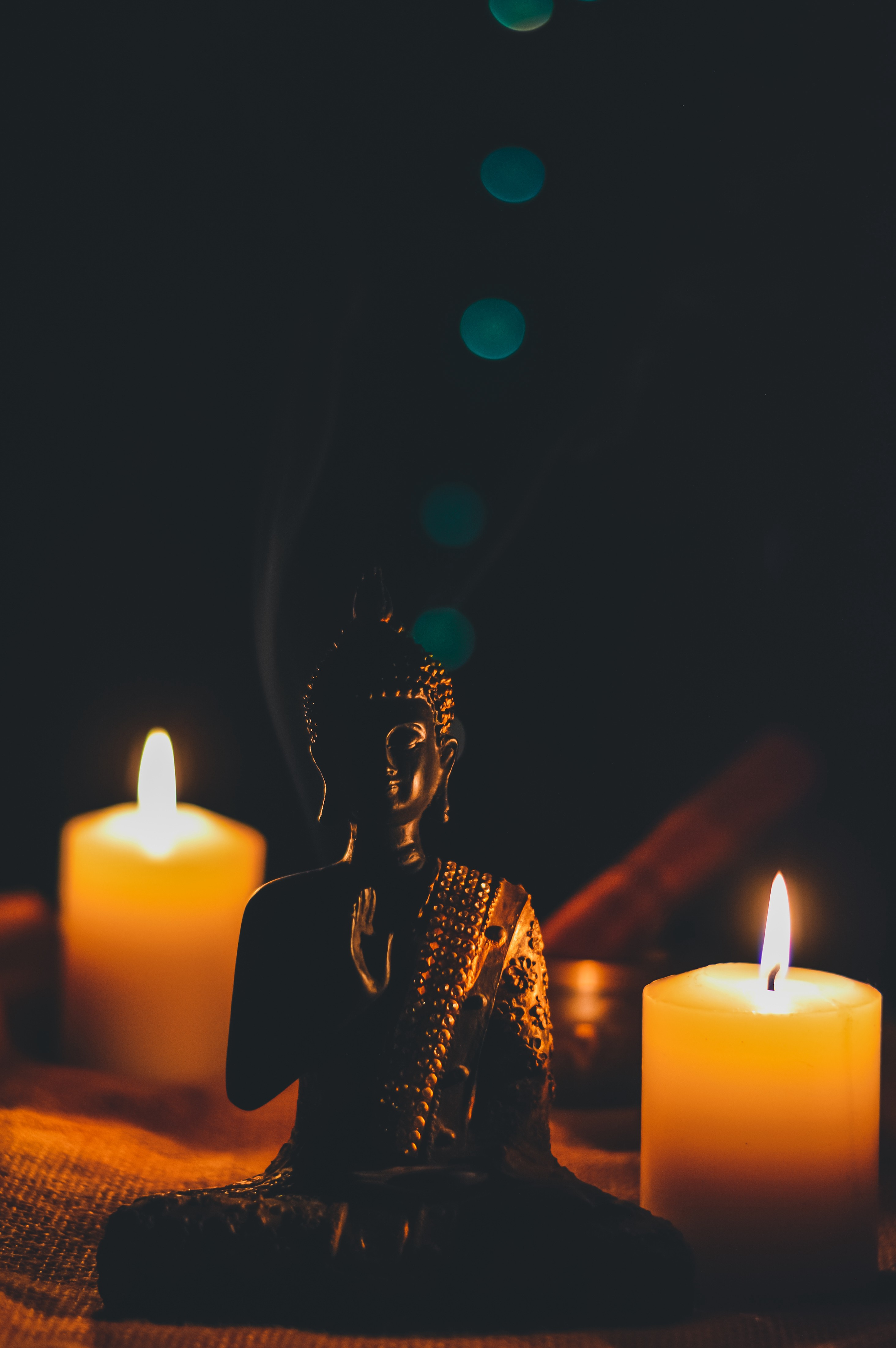 Seated buddha figure in between two lighted candles—One thing keeping me sane during this pandemic