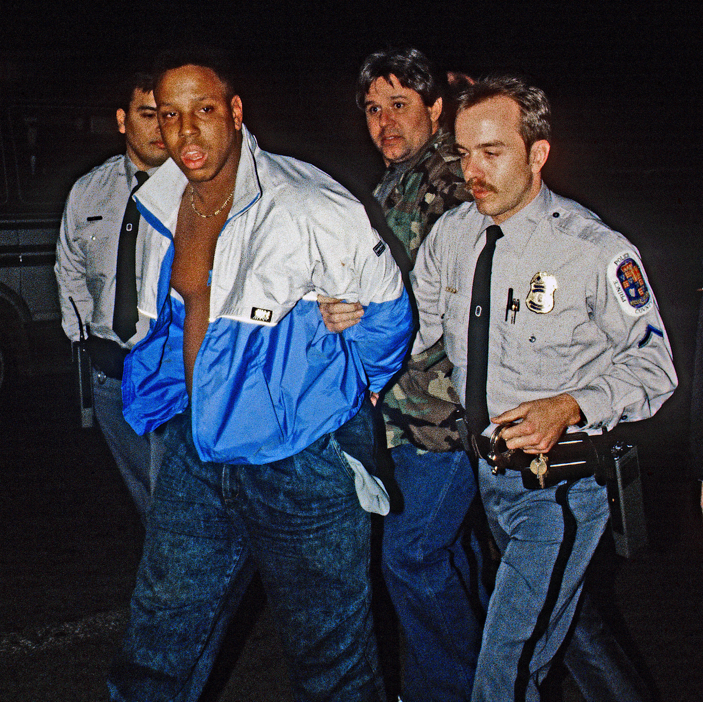 A young African American male being arrested by three white police officers in the 1980s
