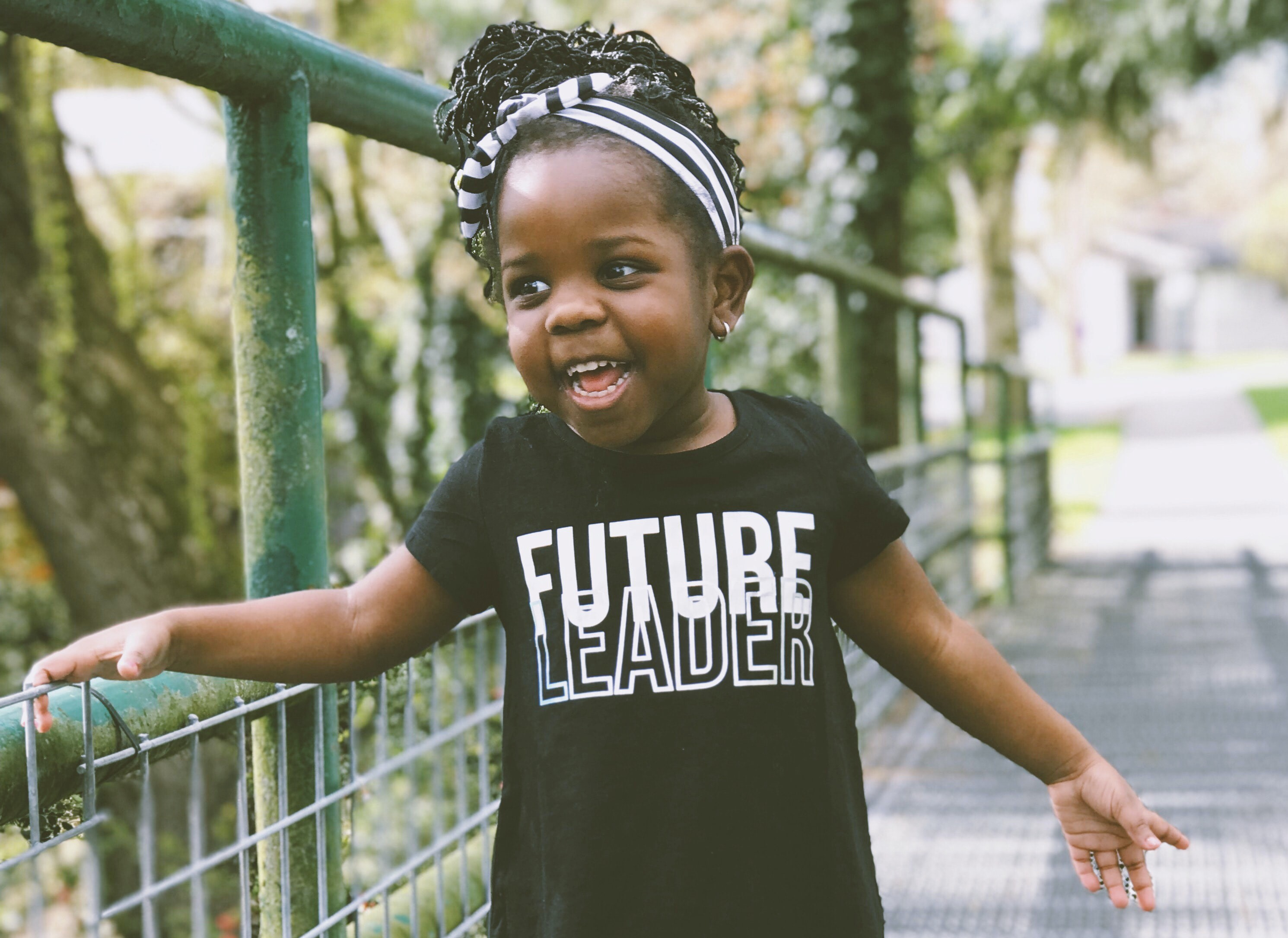 "Excited adorable kid, with brown skin and black braids in a striped headband, in a ""Future Leader"" shirt, on a little bridge"