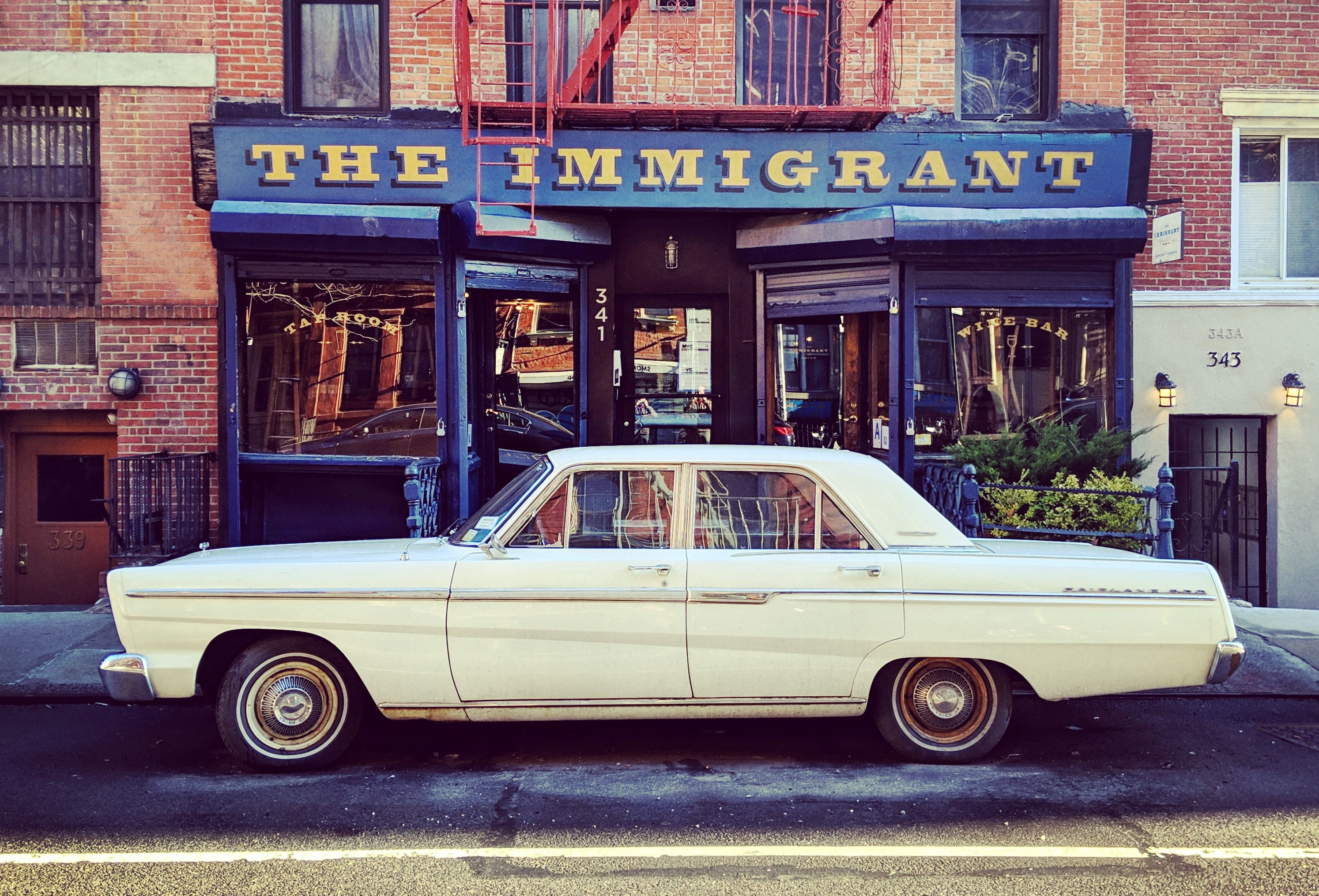 A classic car parked in front of the Immigrant wine and beer bar
