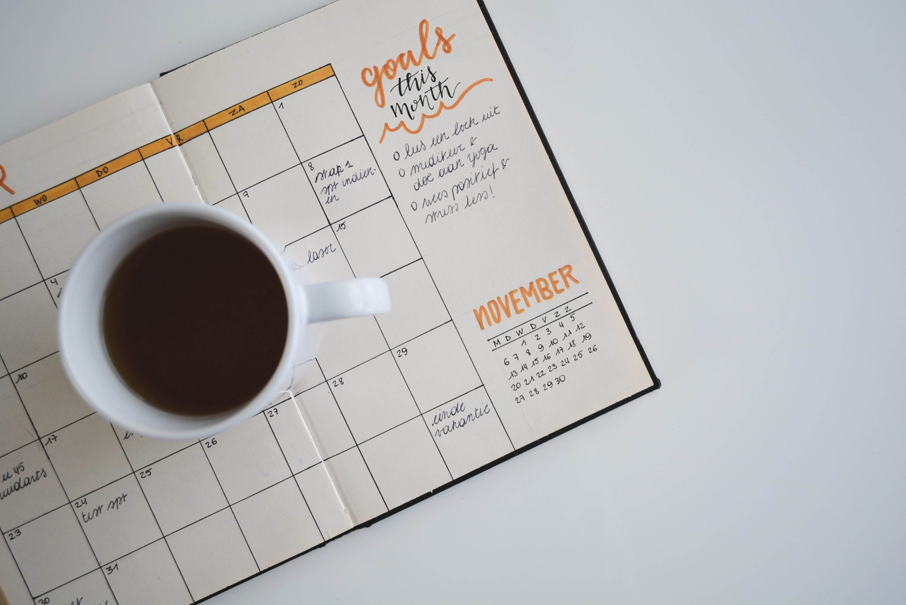 A cup of coffee sitting on a daily planner notebook