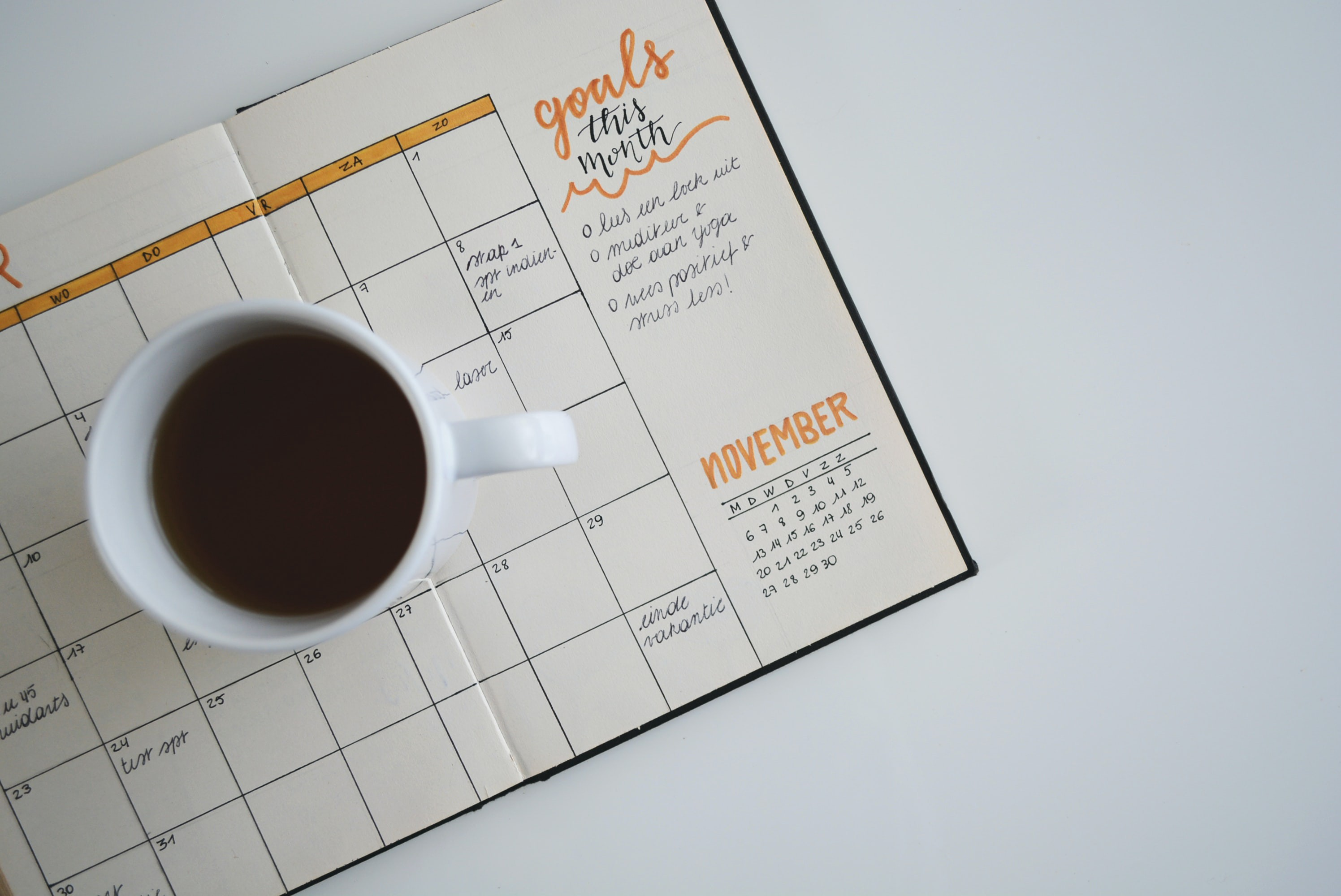 Journal calendar with cup of coffee sitting on top