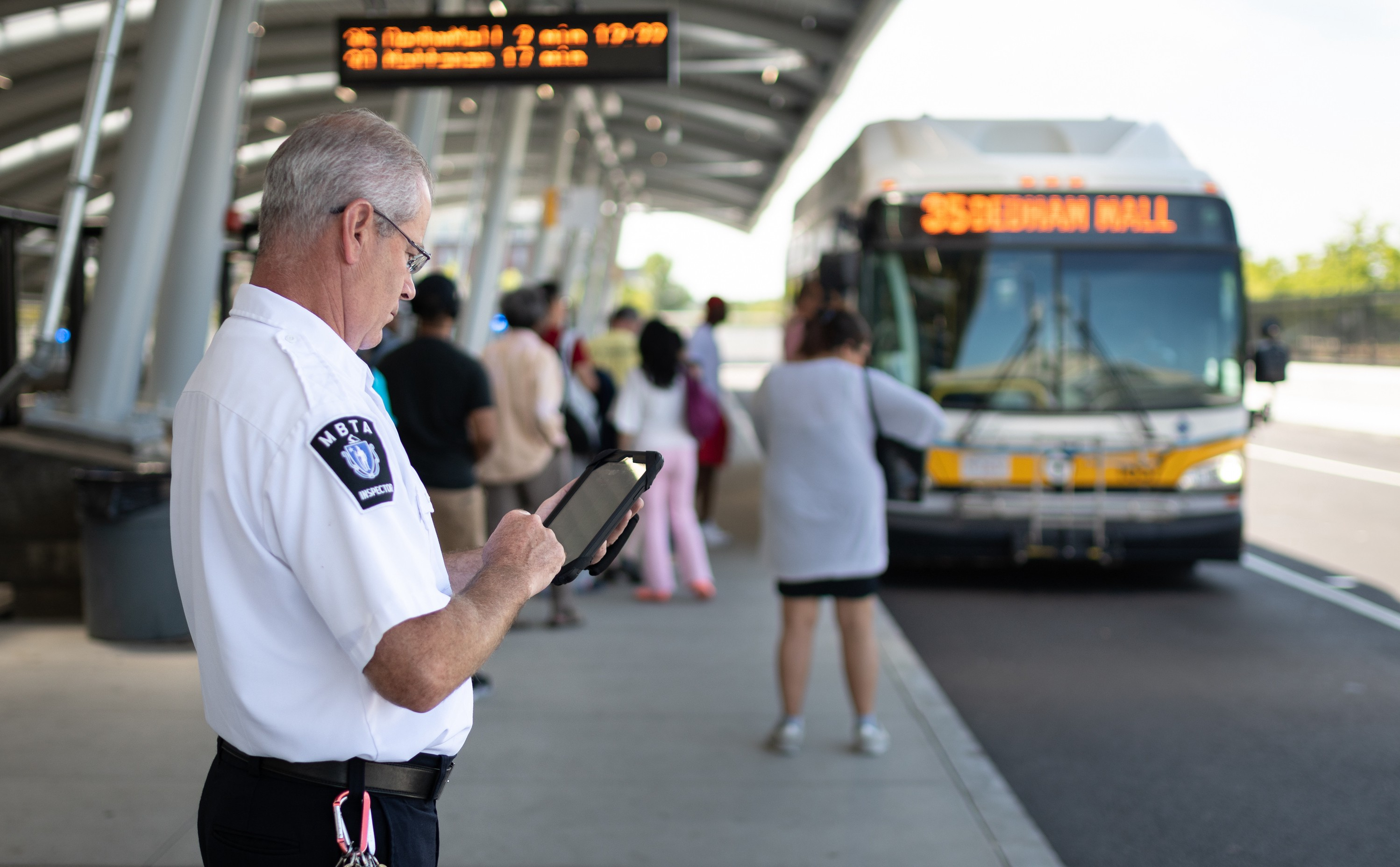 A uniformed MBTA employee uses a tablet at a busway with passengers boarding a bus in the background.
