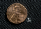 A small amount of white fentanyl is shown next to a much larger penny.