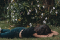 Woman laying face-down on grass in front of a flower bush.